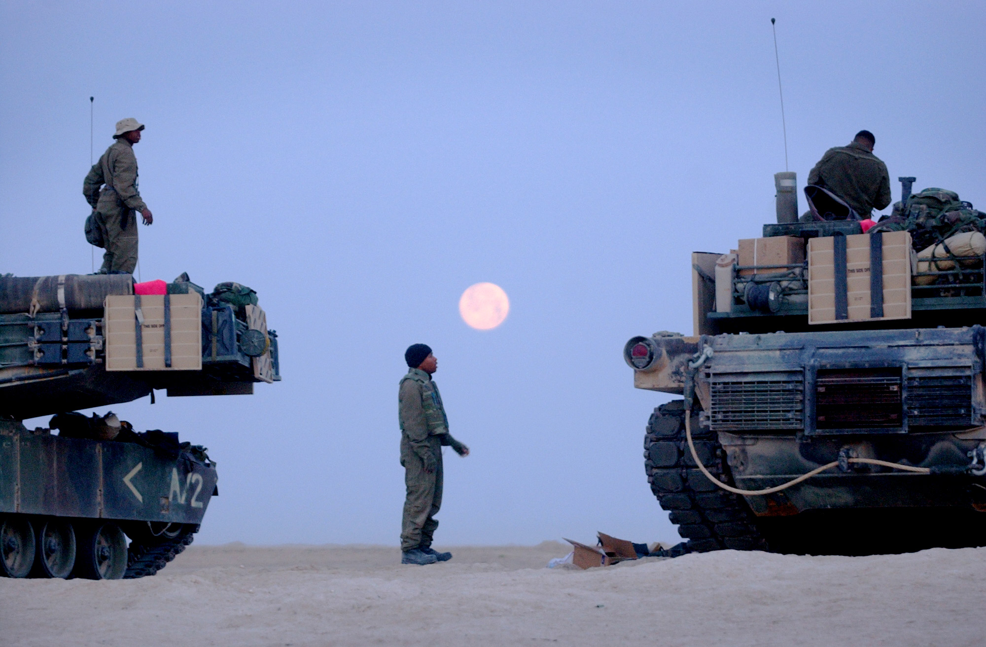 After hearing President George Bush's speech on the radio announcing the launch of the war with Iraq, Marines from the Second Tank Battalion camped in Kuwait prepare before sunrise to move north to the southern border of Iraq in anticipation of the invasion on March 18, 2003.