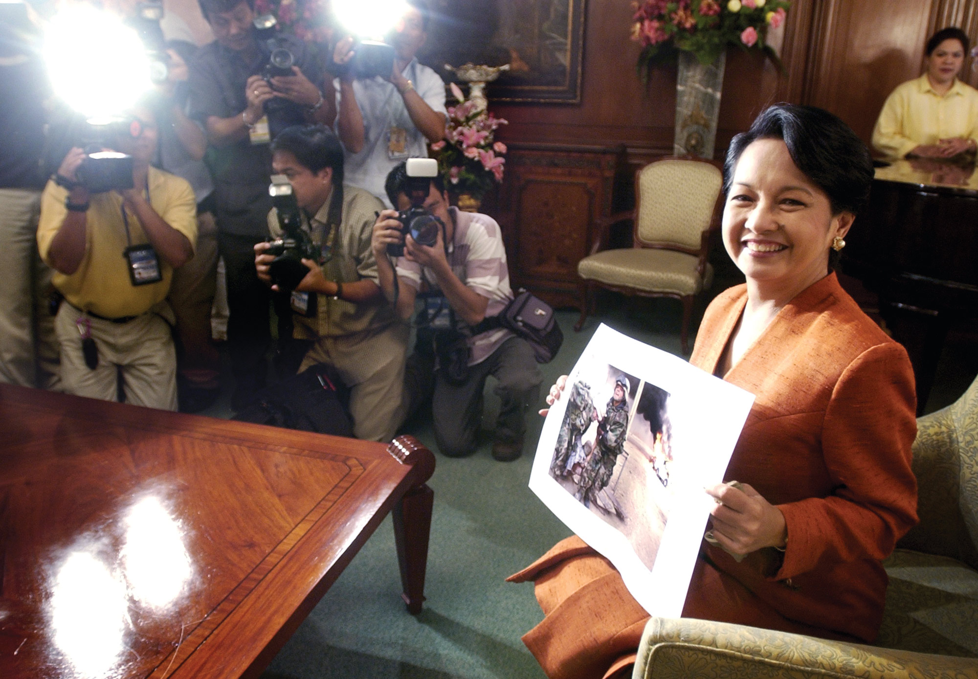 Philippine President Gloria Macapagal Arroyo holds up the 2004 Pulitzer Prize winning photograph by Cheryl Diaz Meyer, during Diaz Meyer's visit to the Malacañang Palace in Manila Philippines, on June 16, 2004. Diaz Meyer is the fourth Filipino to win the Pulitzer Prize.