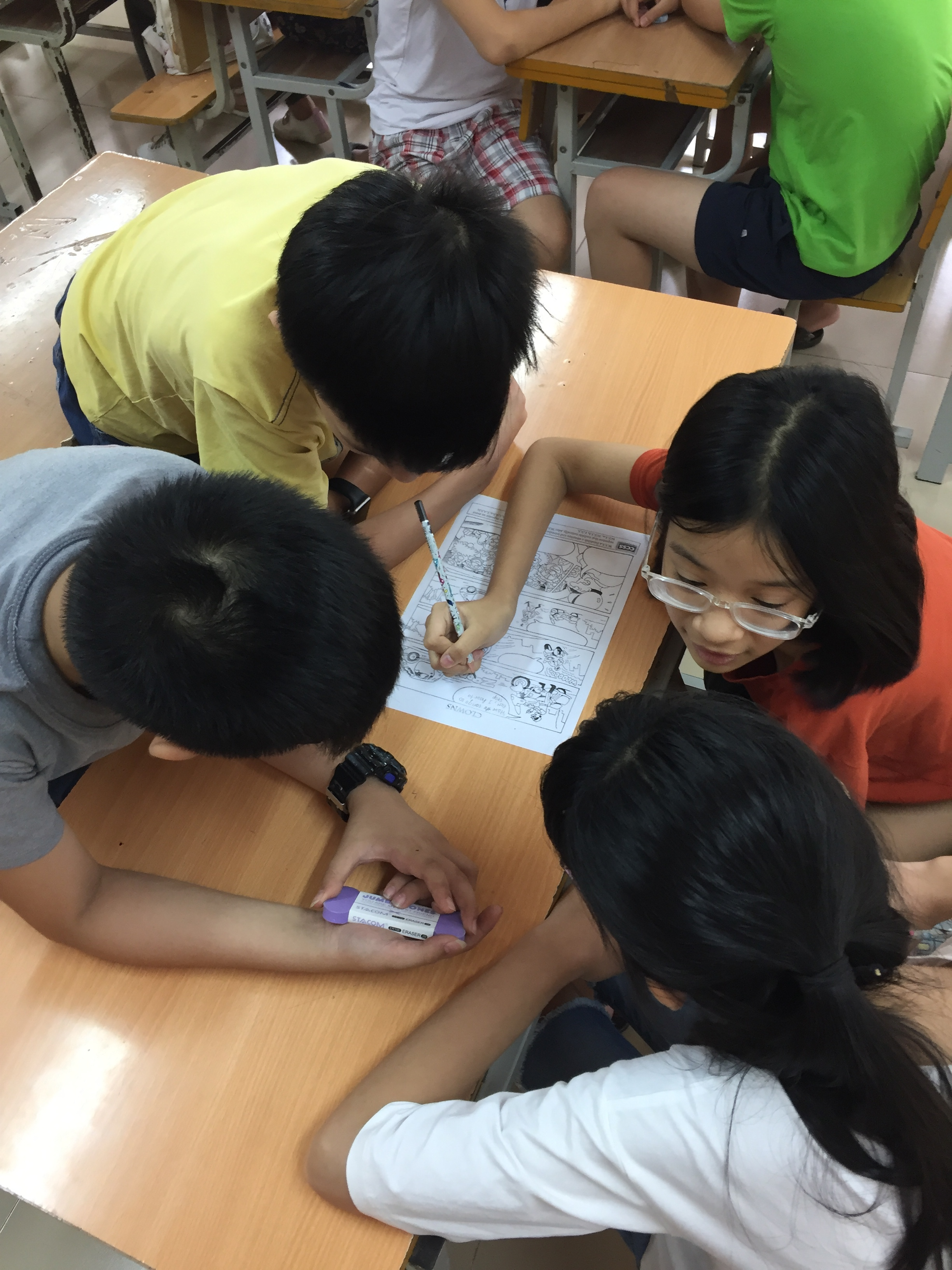 Students from class 6I write words to accompany the blank comics on the worksheet.