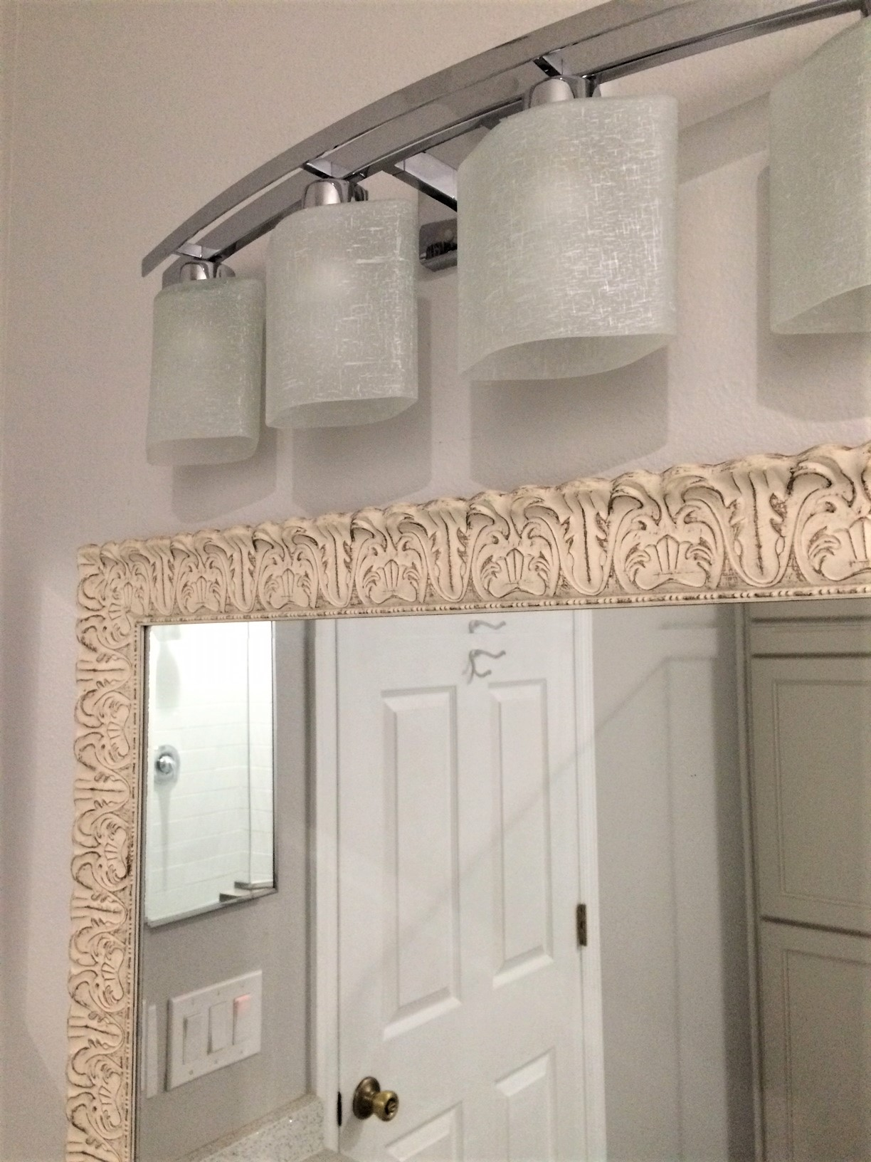 Long vanity mirror enhances the feeling of a larger bathroom.  Modern vanity light with silver finish to combine with the existing fixtures and parts finish