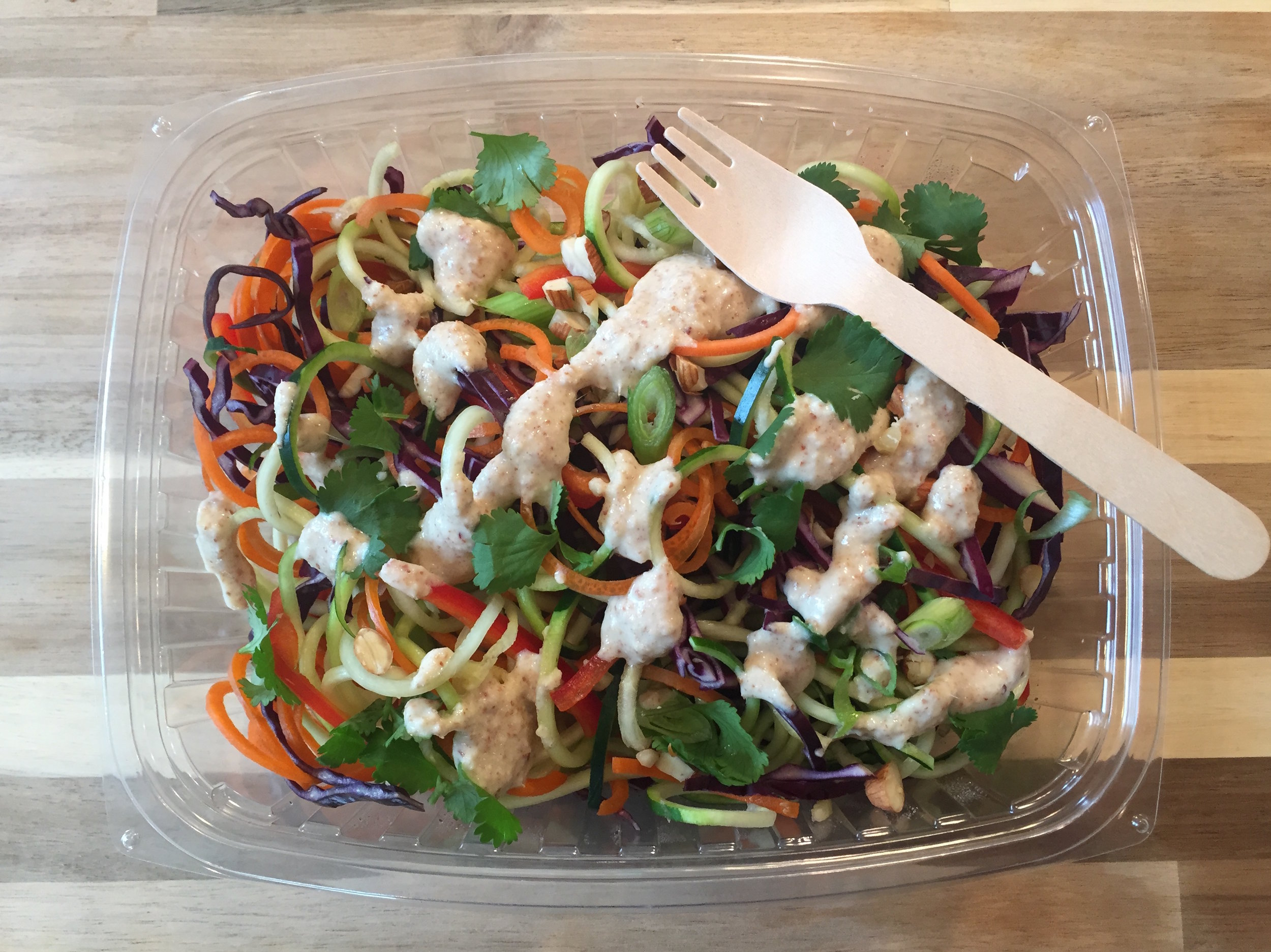 Raw Pad Thai - Zoodles, carrot curls, bell pepper, red cabbage, scallions, almonds, and cilantro, with a ginger almond dressing.