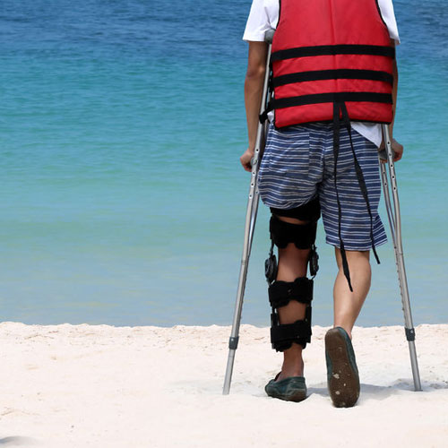97993924-disabled-man-with-crutches-while-travel-on-the-beach-ocean-views-background-small-500x500.jpg