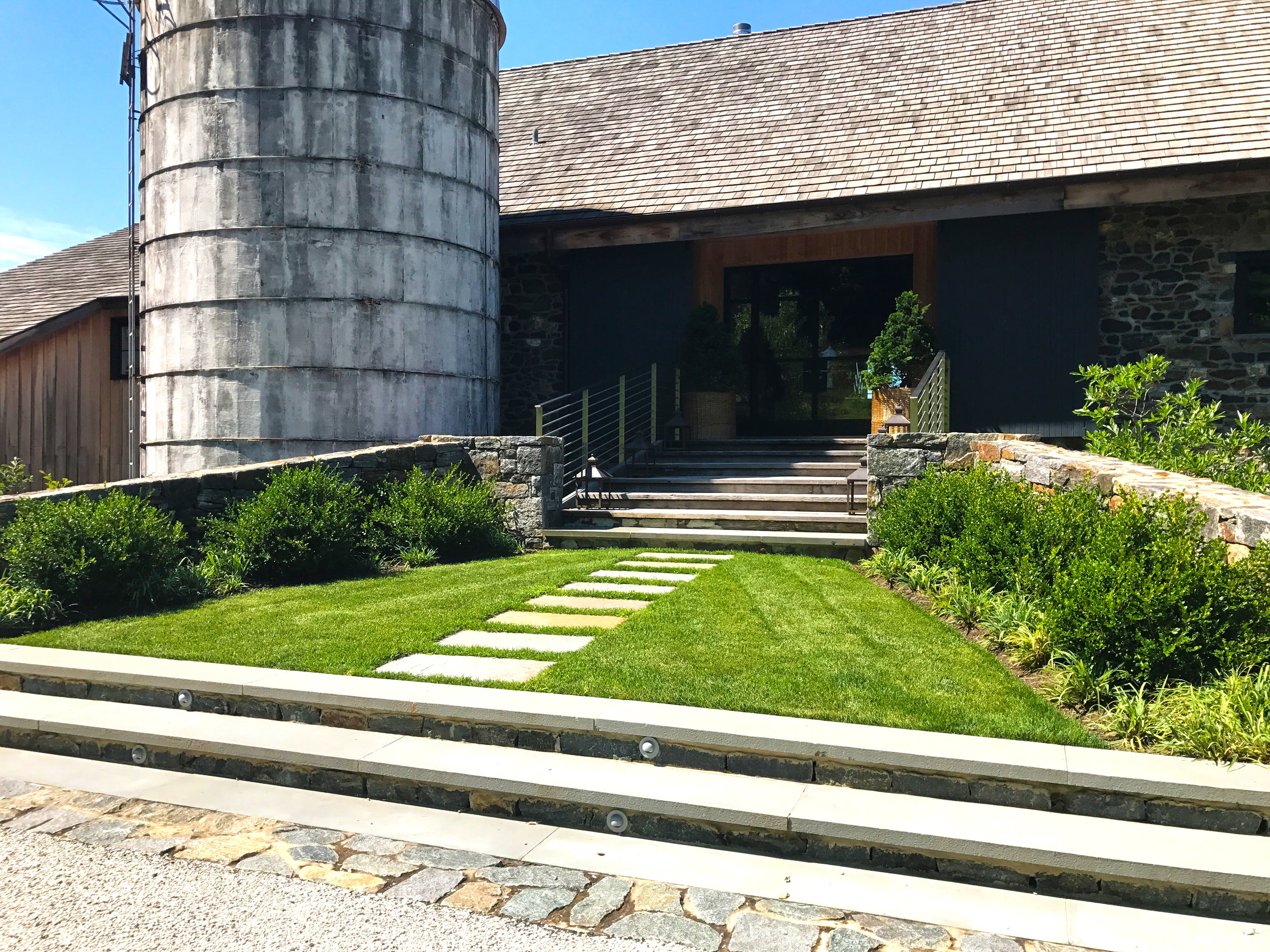 A lawn ramp to the front door stretches over a sunken shade garden and breakfast terrace.