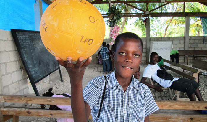 """Prophet, age 14, shows off the """"vowels"""" ball used in GOALS literacy class. This is the first time Prophet has ever been to school."""