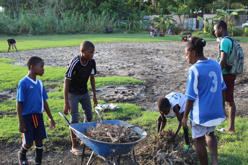 GOALS kids cleaning debris off the soccer field after Hurricane Matthew