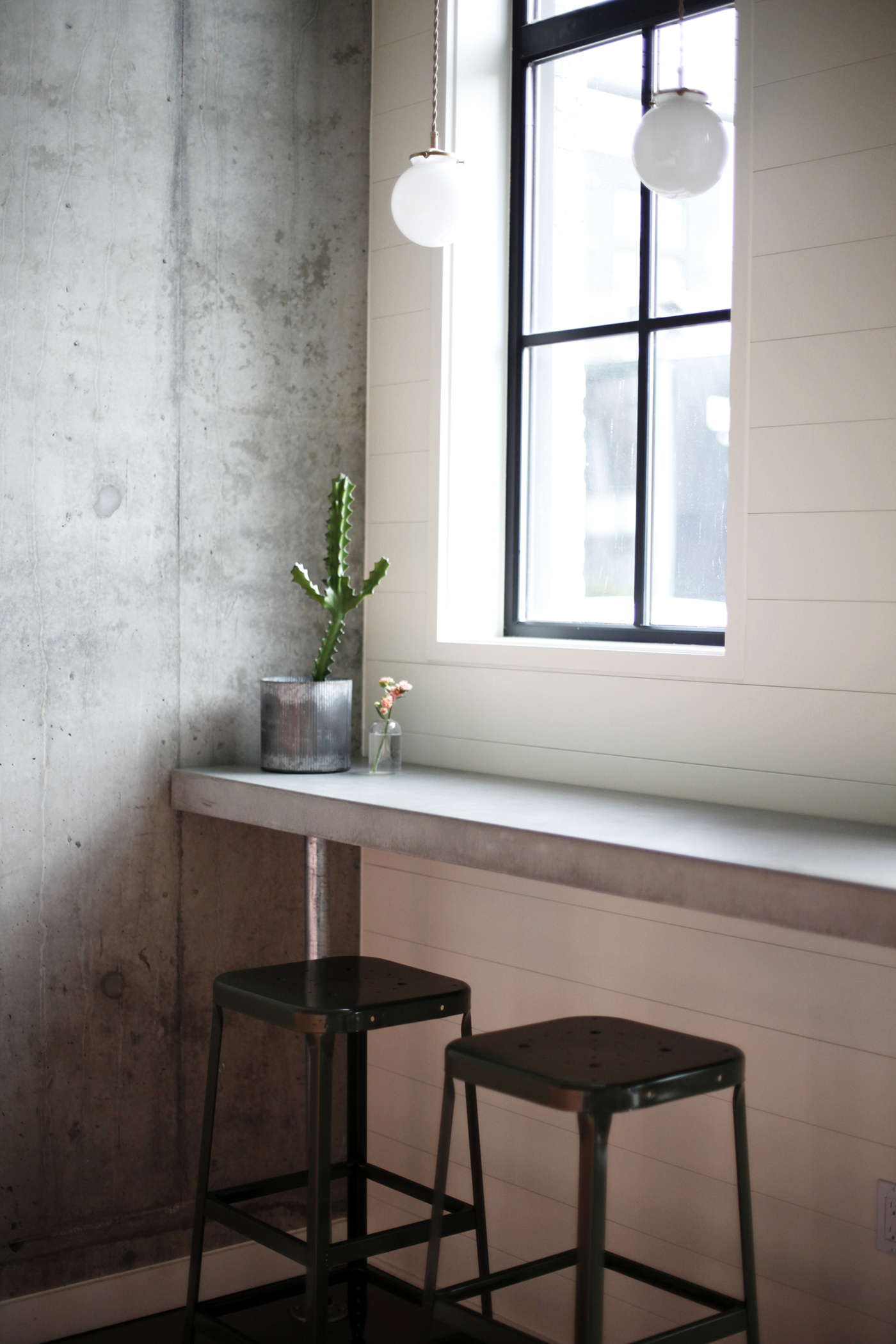 AN IDEAL BACKDROP - Katie's team applied wood panels from floor to ceiling and cased around each of the windows and doors.They decided to work with the existing concrete retaining wall, as it was an ideal backdrop and contrast to the brass framed mirror, and installed concrete counters and floors to play up the bright scoops of Frankie & Jo's ice cream.