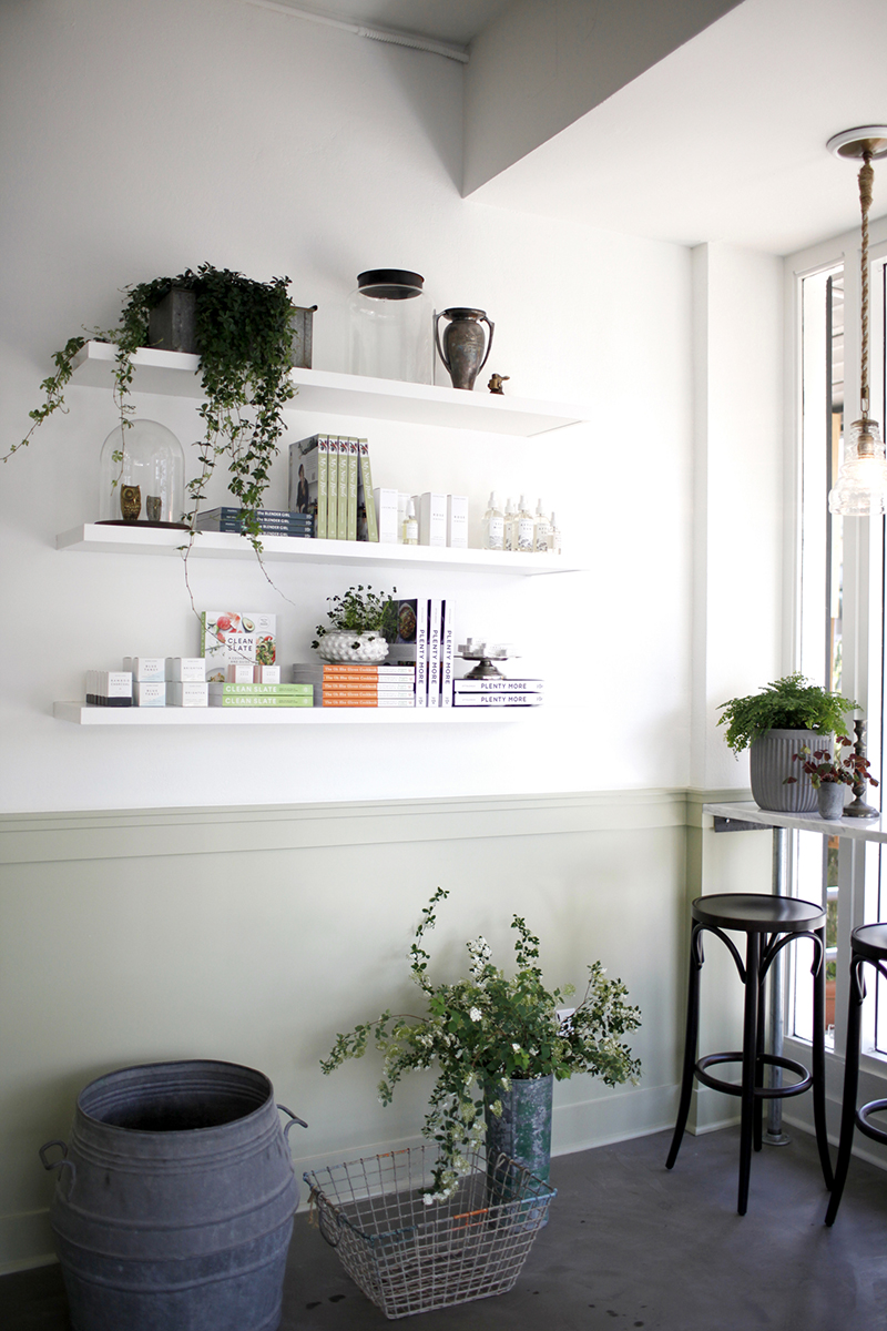 A THOUGHTFUL DISPLAY - A thoughtfully arranged corner showcases a unique array of apothecary items, including cookbooks, herbal remedies, and organic beauty products.