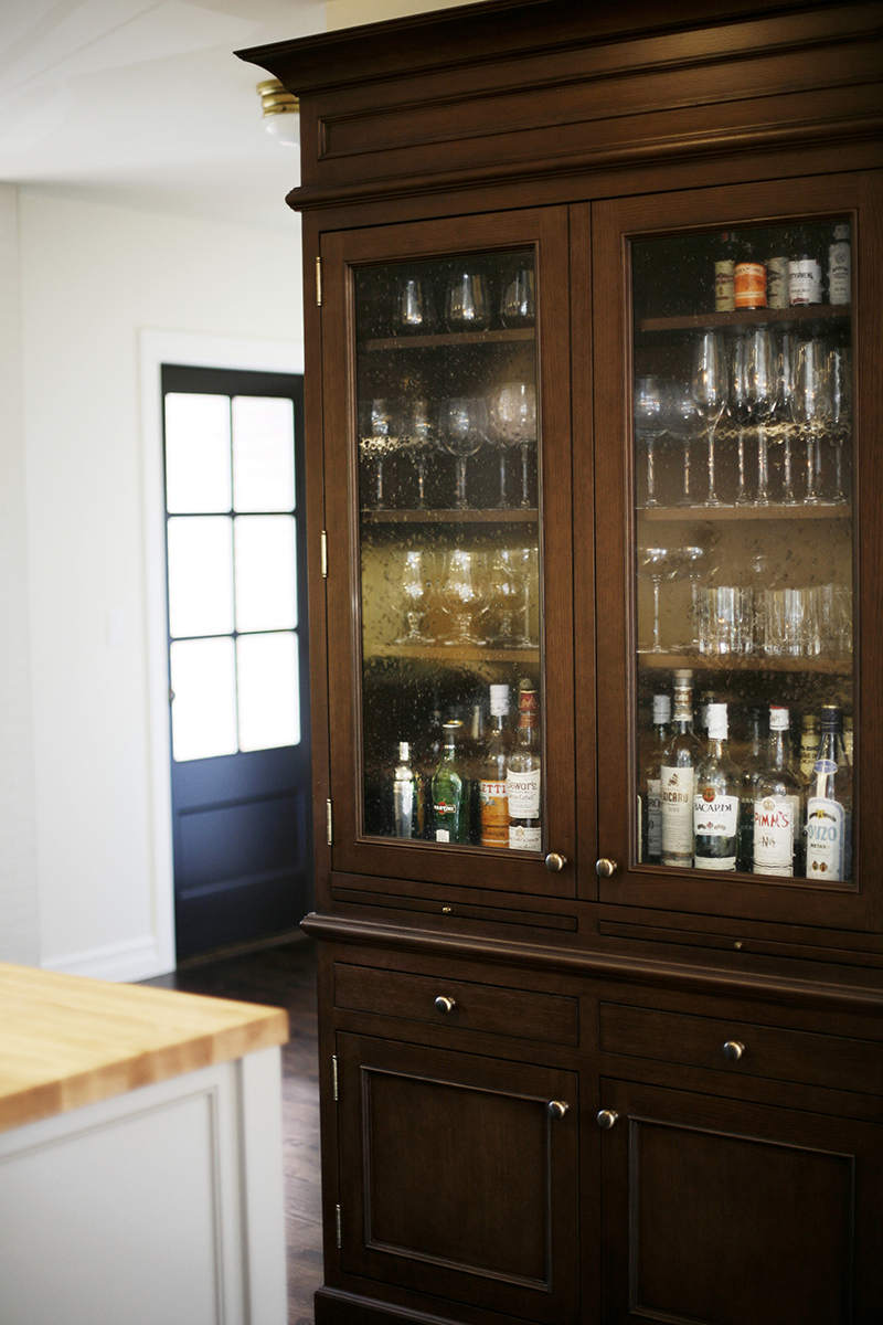 CUSTOM CABINETRY - Katie designs the custom cabinetry around the client, a close knit family of five, and how they live. A stained oak bar cabinet is created to feel like a separate piece of furniture, reminiscent of a family heirloom.