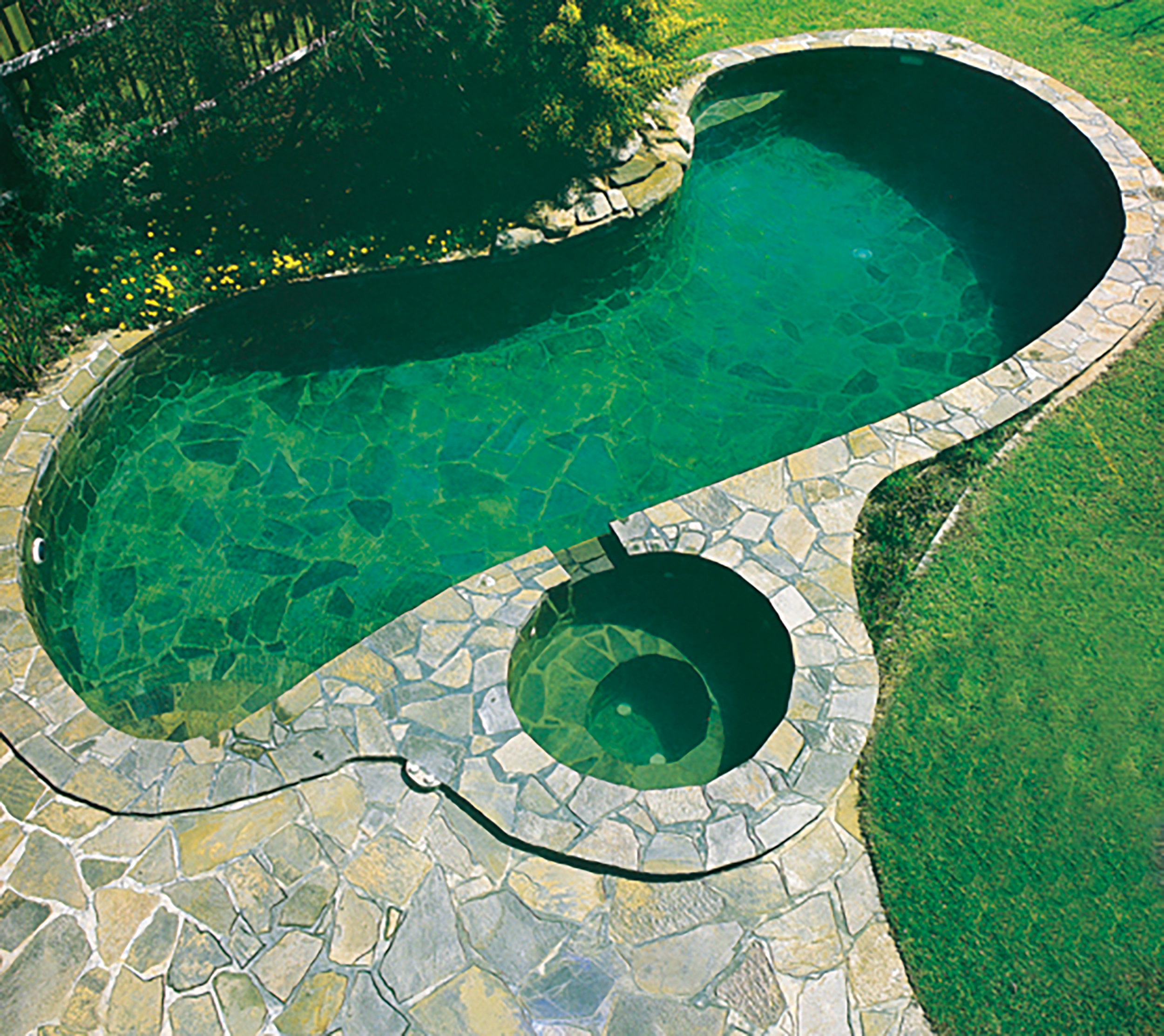 Crazy Paving in Wistow Stone around Pool and Spa as Coping