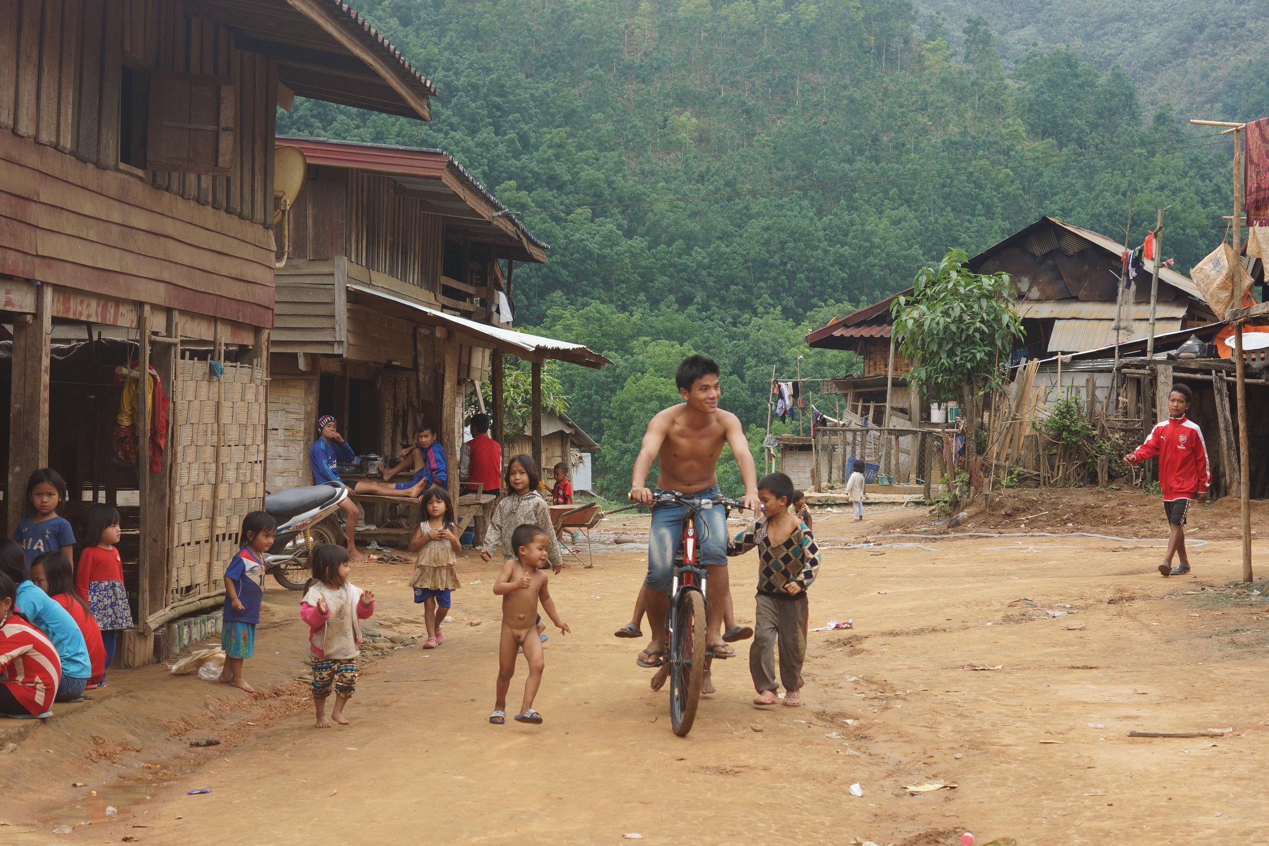 A Lakkham-Kao villager taking a joy ride on my mountain bike, village kids in pursuit.