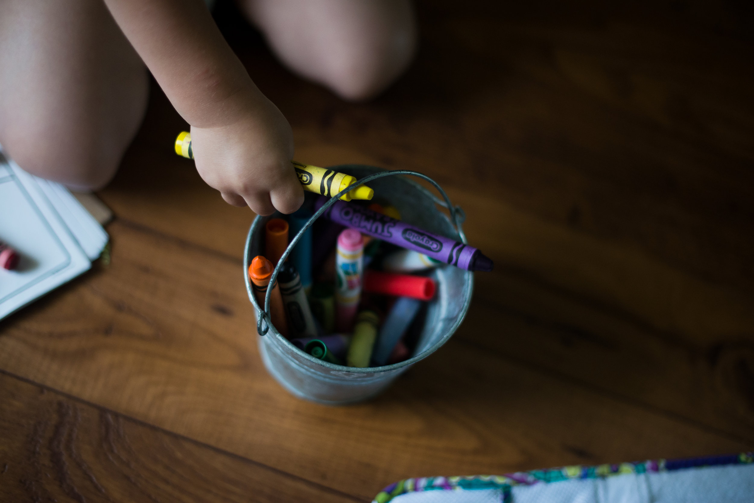 toddler hand reaching for crayons in bucket