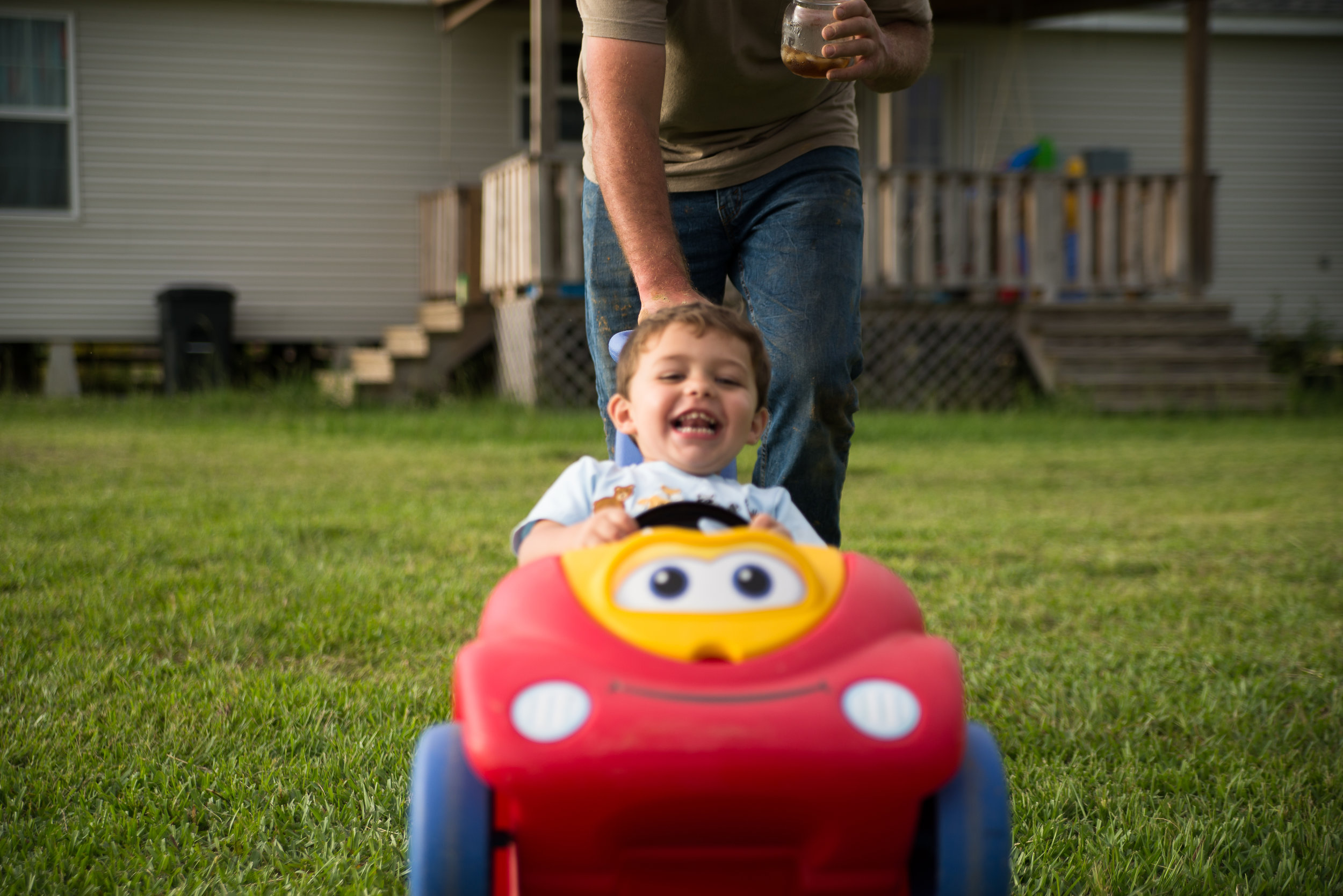 boy being pushed in toy car