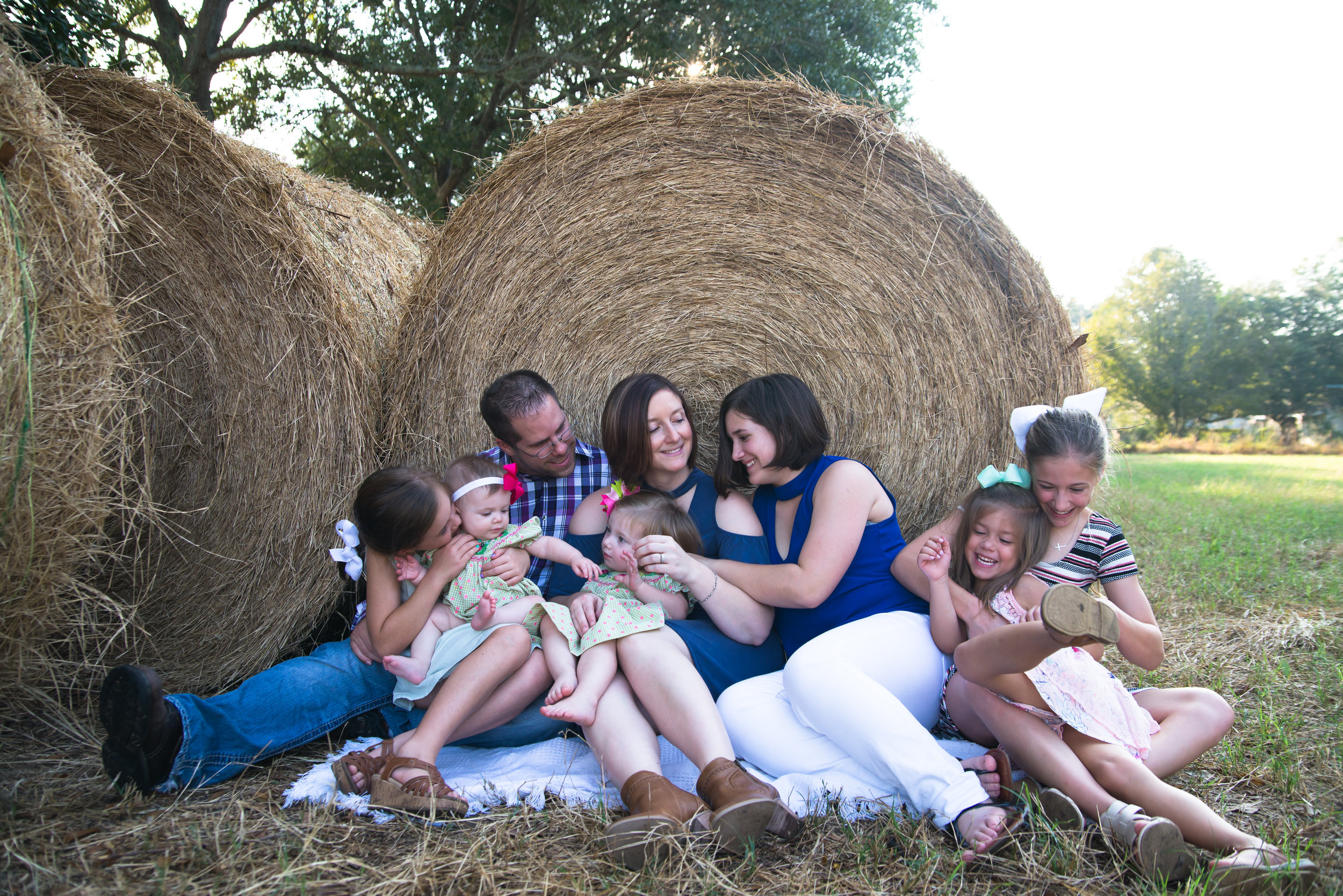 lifestyle family portraits, family sitting near hay bale, Louisiana family photography