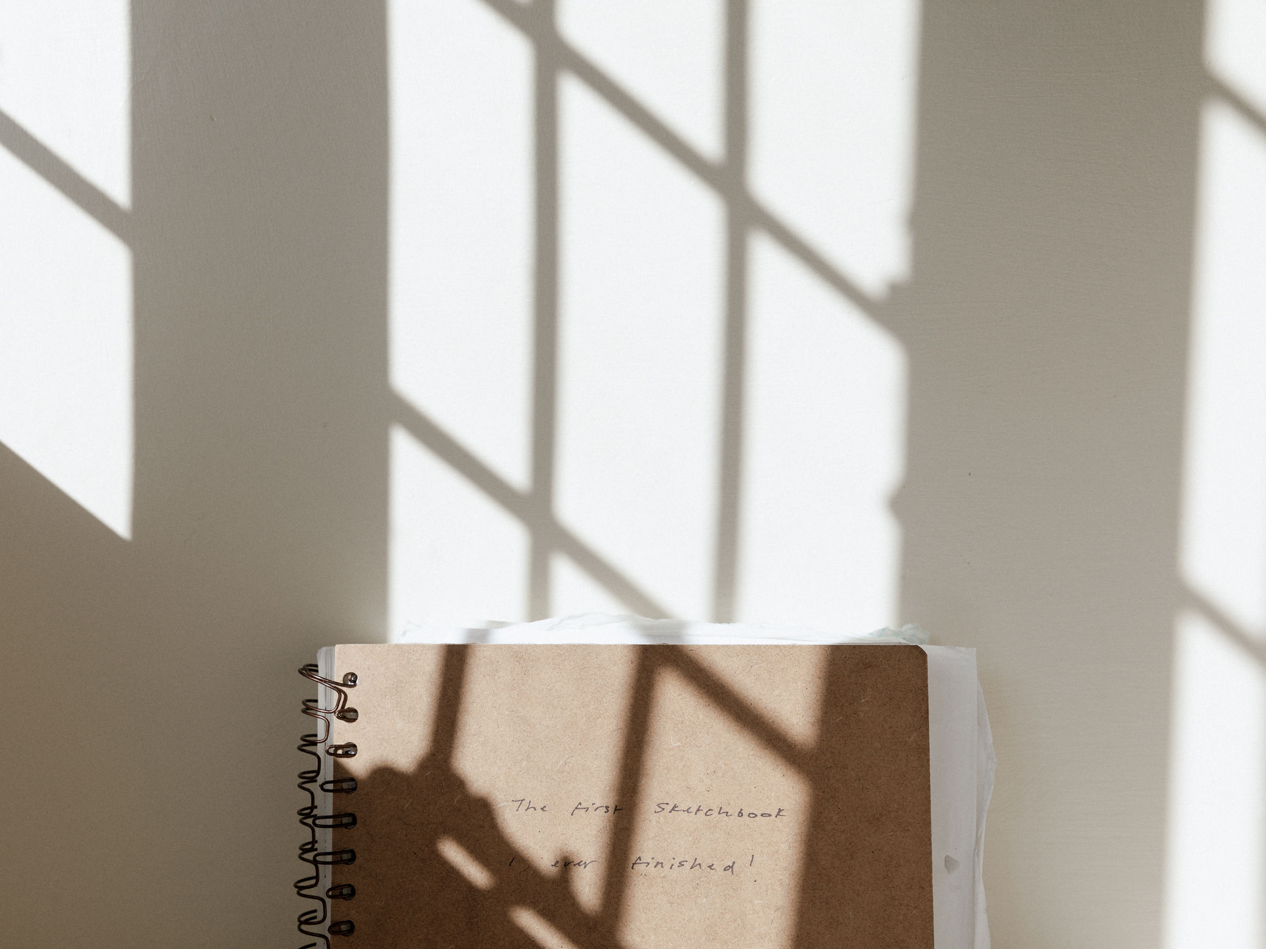 Photo of sketchbook against a wall with a shadow of a window