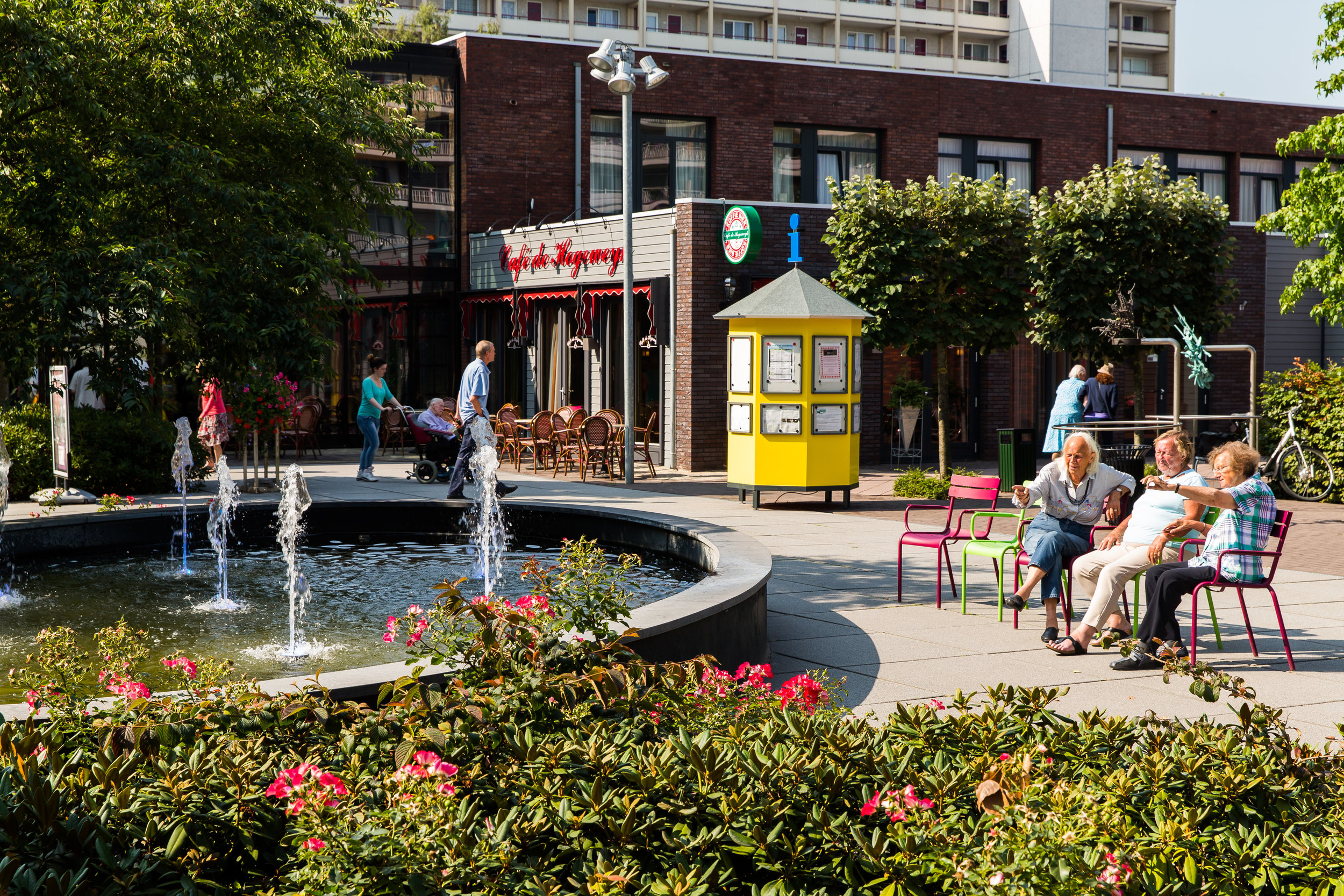 Residents of de Hogeweyk sitting by an outdoor fountain.
