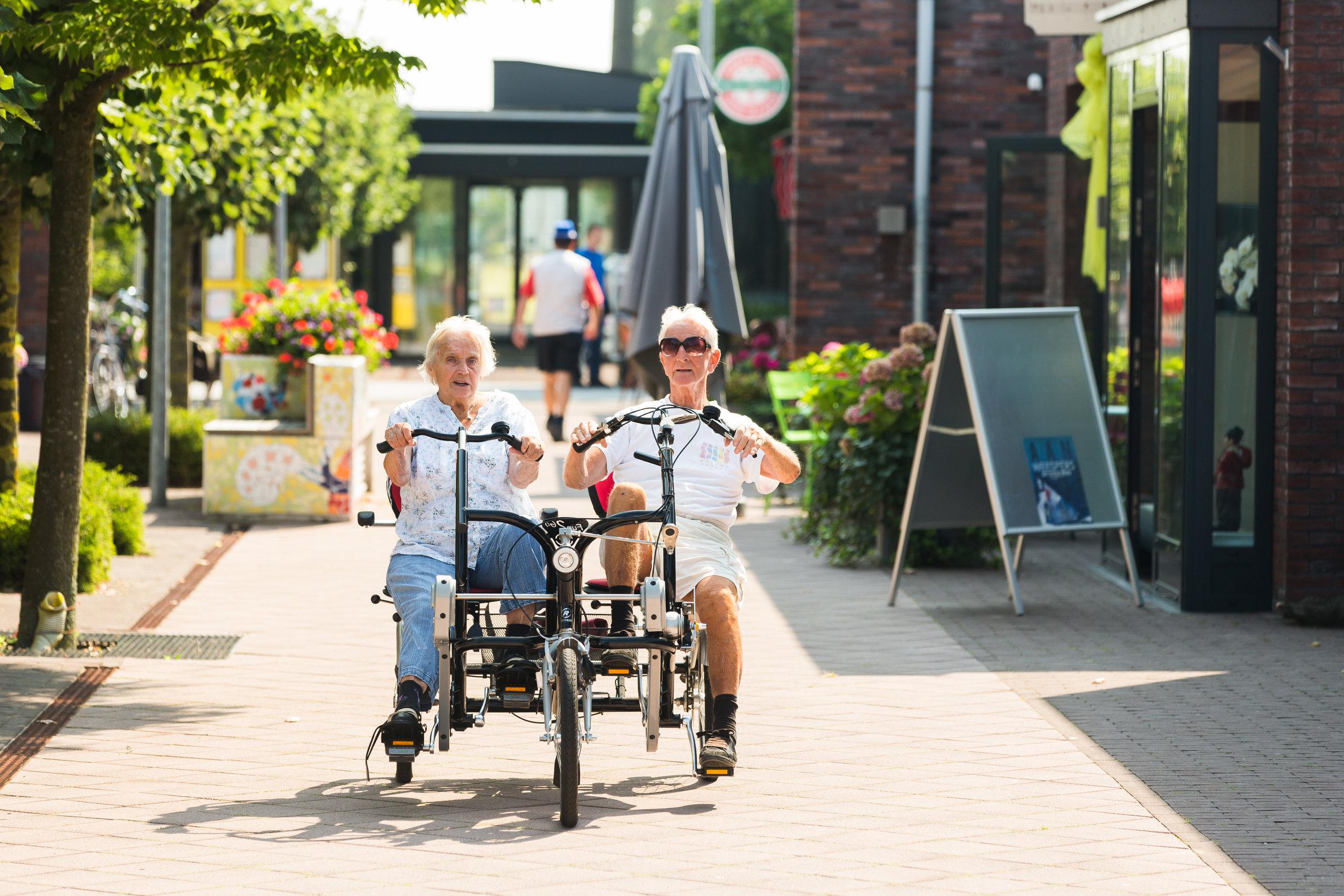 Residents riding a side-by-side bike at De Hogeweyk.