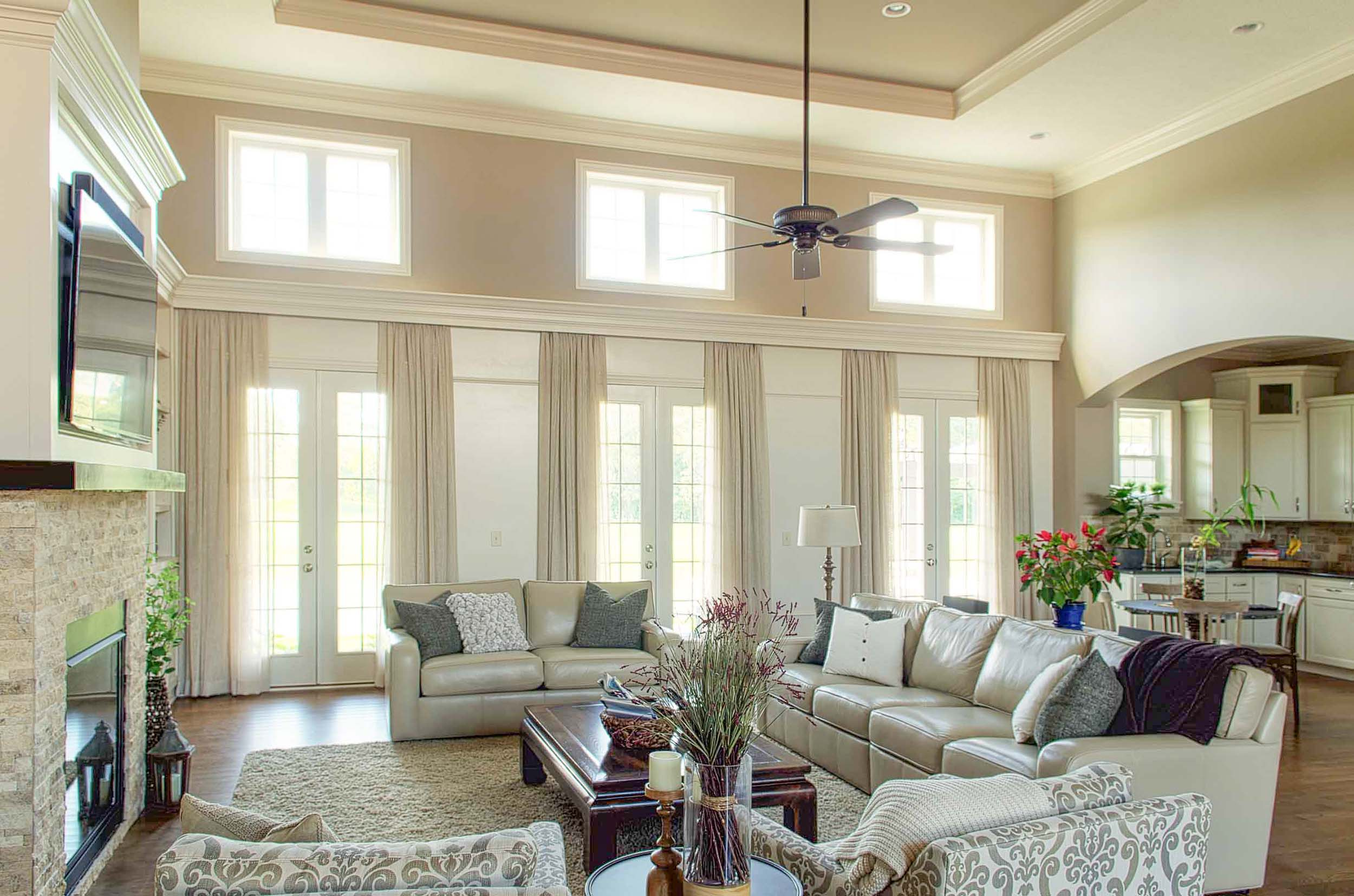 Elegant living room with large window and high vaulted ceiling