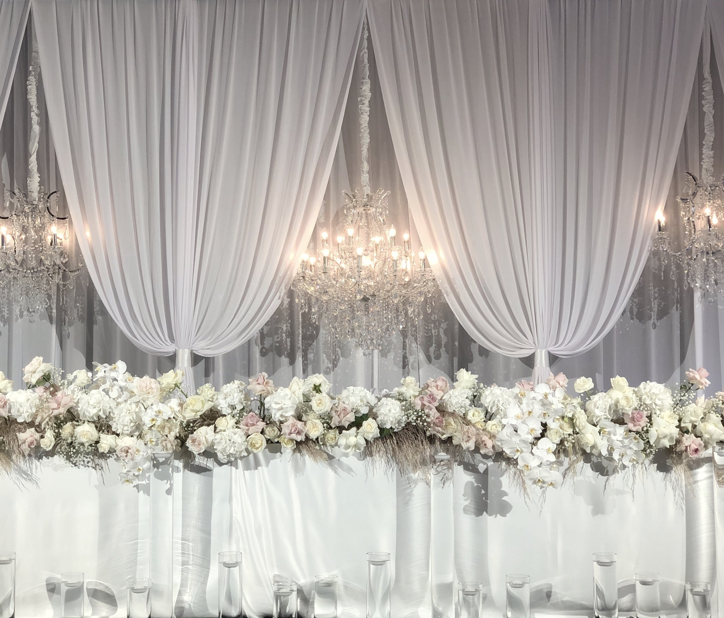 draped backdrop with chandeliers