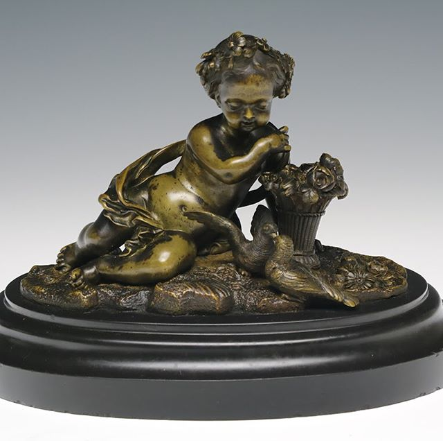 A finely cast and chased continental figure of a putto, or cherub, shown adorned with a drape. The figure is depicted leaning over a basket of flowers and looking down at a pair of doves on the ground. Mounted on the original elliptical black marble base. . . 7 in. (18 cm.) tall . . DM for inquiry. Link in profile. . . #antiqueart #antiquedealer #antiquestyle  #antiques #decorativearts #antiquesforsale #putto #cherub #cherubs #drapery #patina #frenchantique #frenchantiques #objetdart #antiquedecor #vintagedecor #frenchdecor #frenchstyle #homedecor #parisian #fineart #sculpture #bronze #antiquebronze #bronzesculpture #19thcentury #19thcenturyantiques #1800s #interiordecor #interiordesign