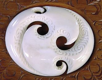 A carving showing the use of cut-out shapes with plain and textured surfaces to portray balance in multiple aspects