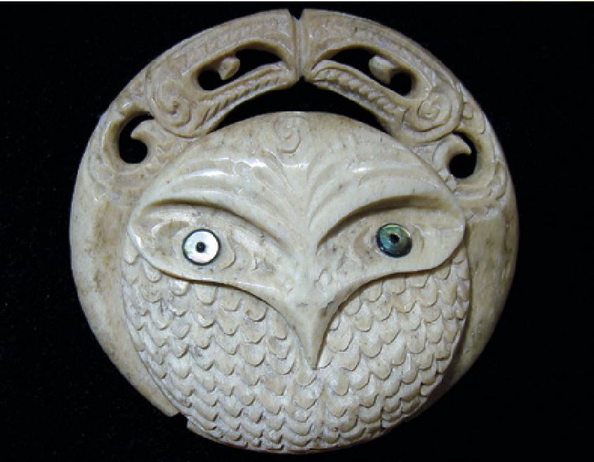 Owl carved as one of a set of circular guardian figures