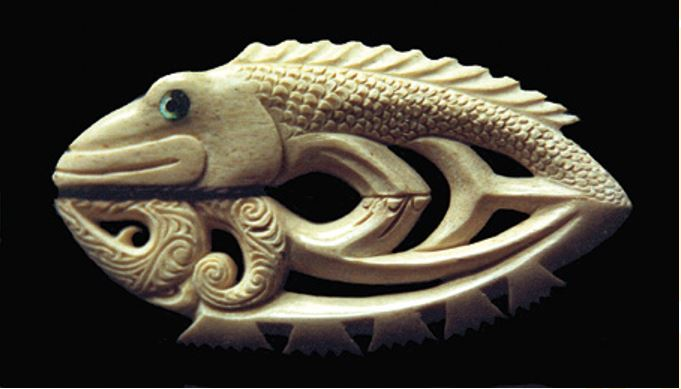 A fish looking at its reflection. The reflection is carved in the old Māori style, with dorsal fins represented as stylisations of face profiles.