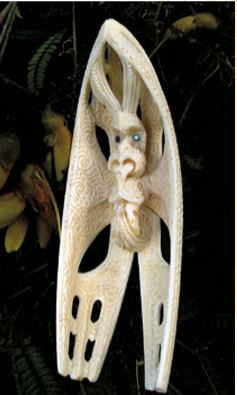 Both sides of a whale-tooth carving of the atua Kahukura Uenuku