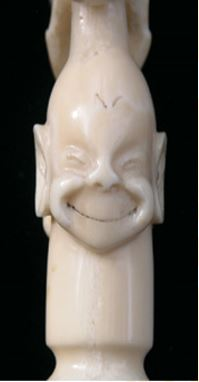 An Inuit dog whip handle carved in Alaska in the early 1900s by Happy Jack, showing detail of a Billiken