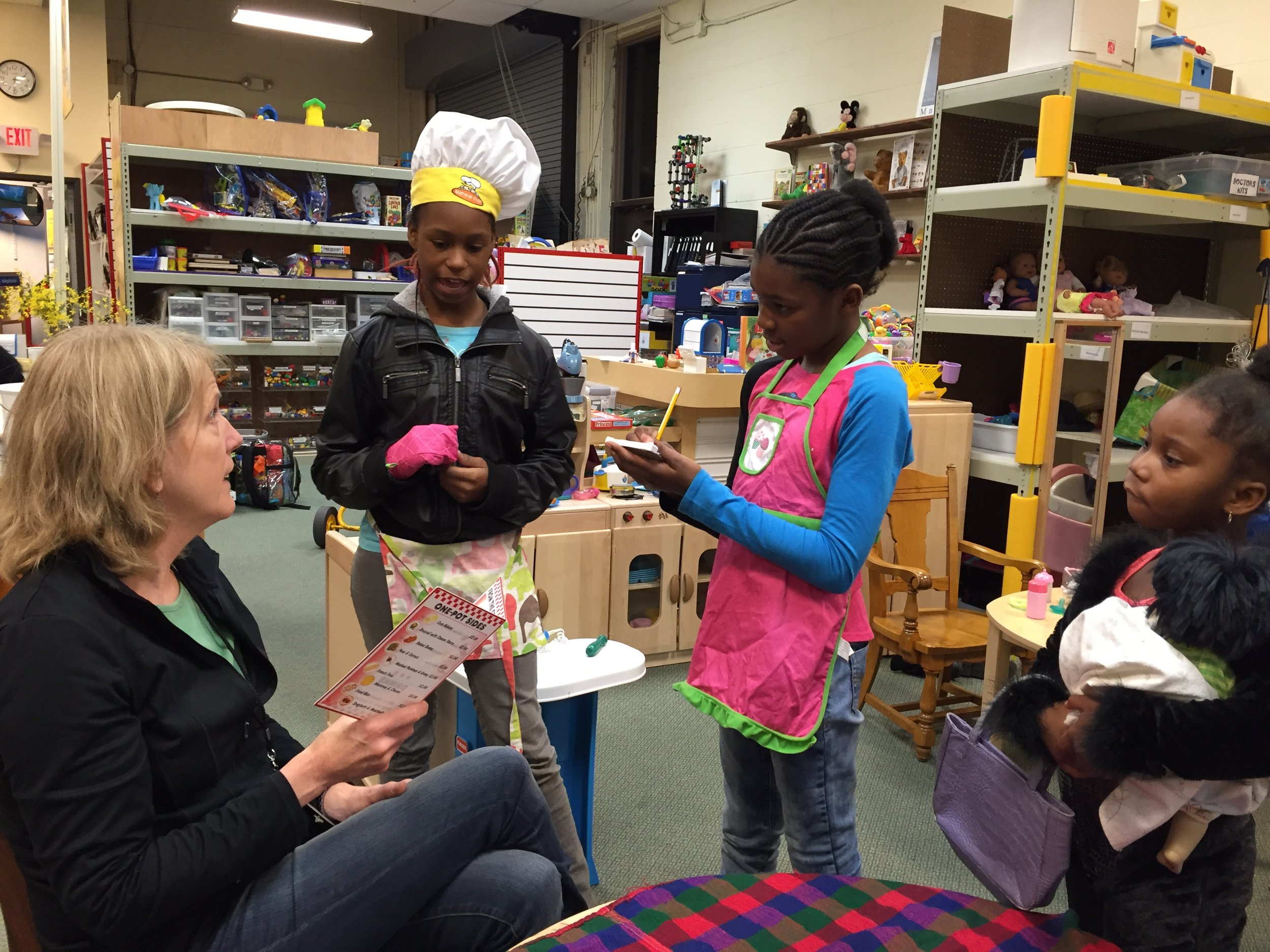 Staff helps children deepen their imaginative, dramatic play and literacy skills. -