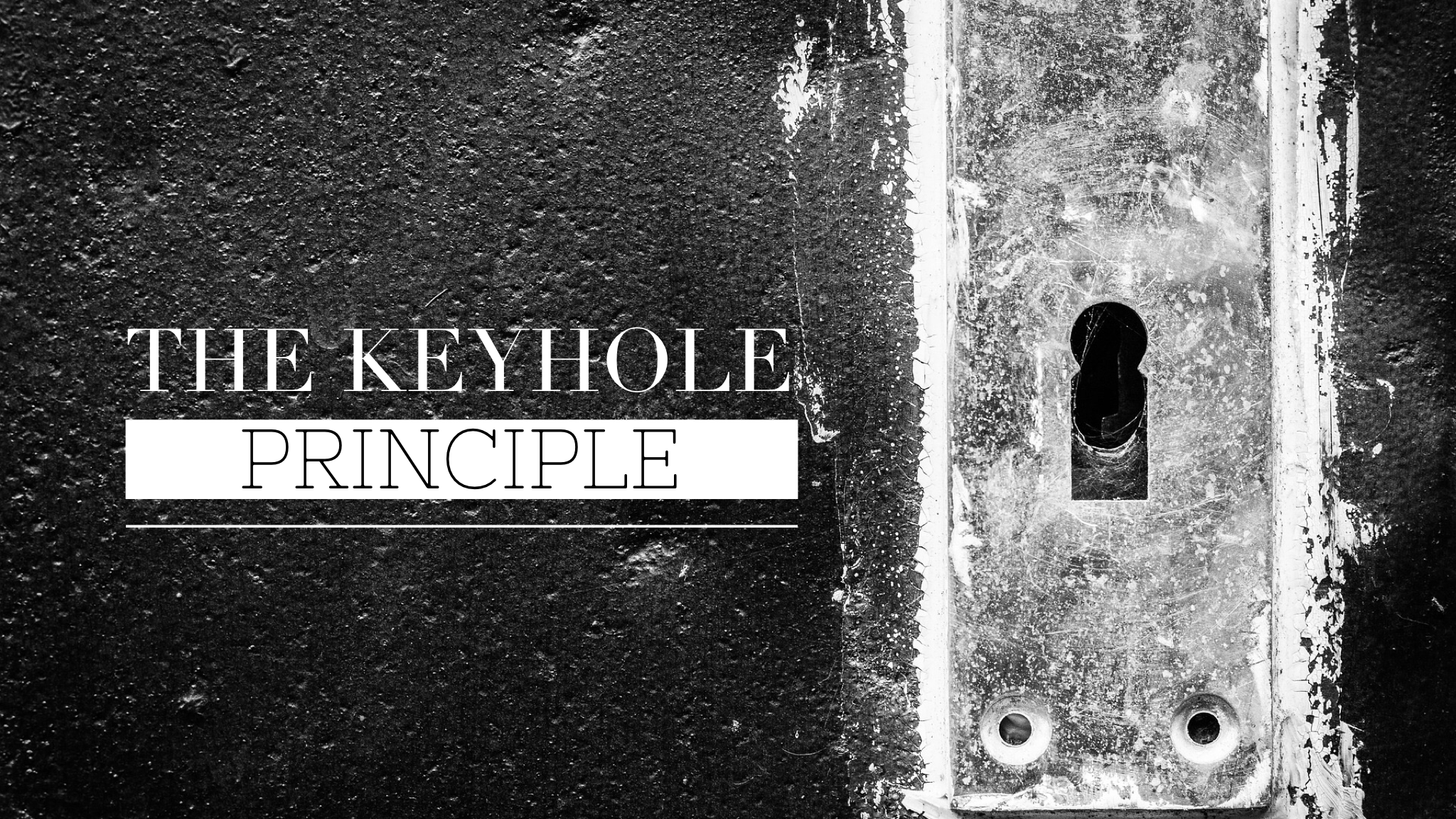 Black & white image of a wall with an antique keyhole plate.