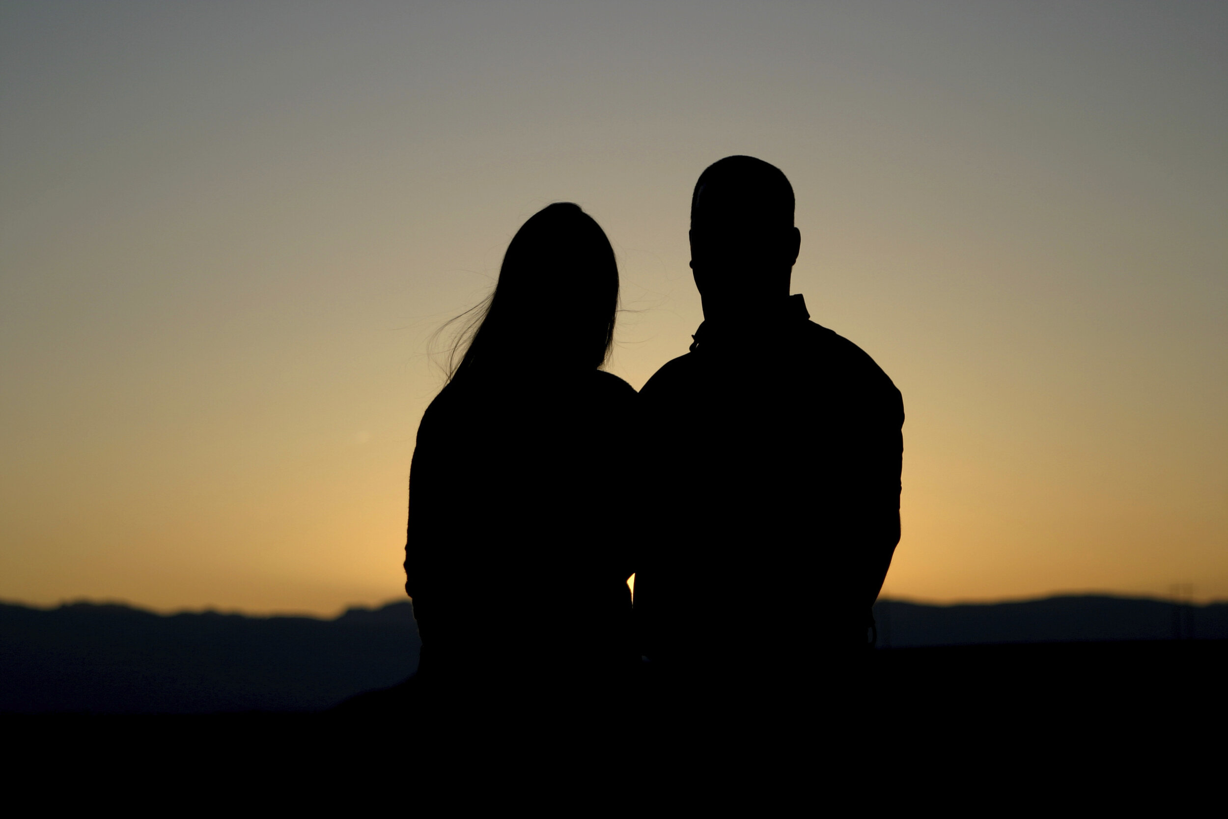 Silhouette of a couple against a sunset background