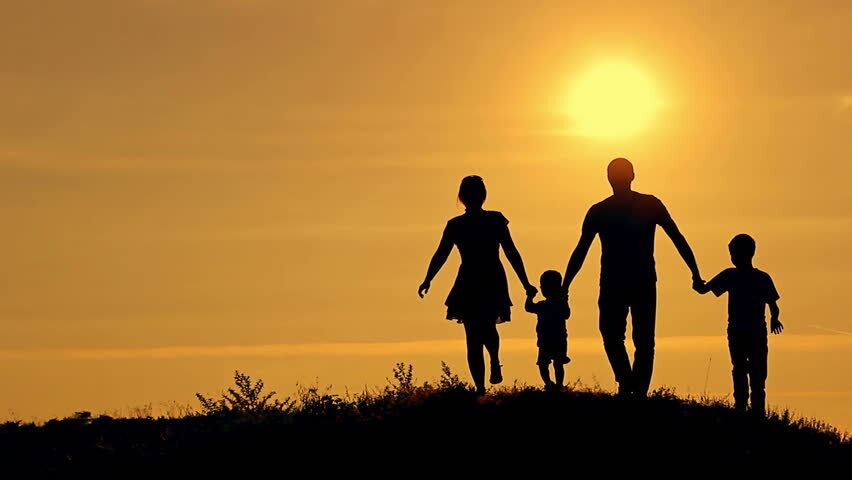 Silhouette of four people, two taller and two shorter, holding hands and walking into a sunset.