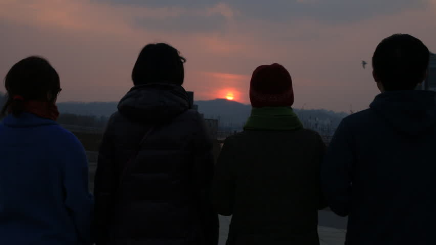 Silhouettes of 4  people looking at a sunset