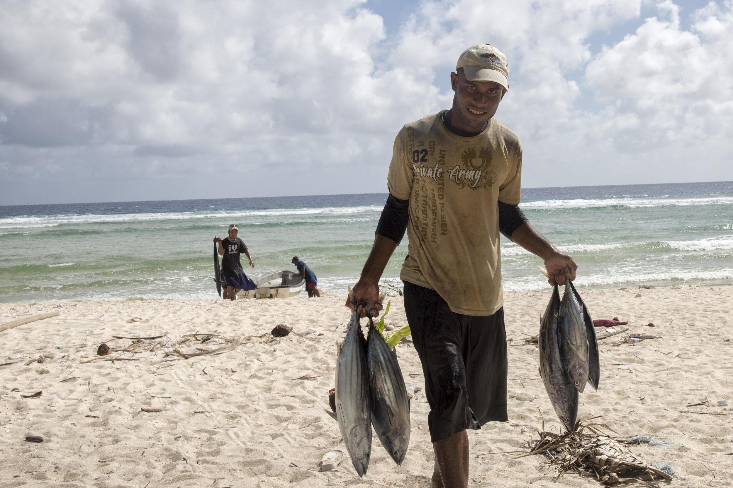 A Micronesian fisherman carrying tuna.