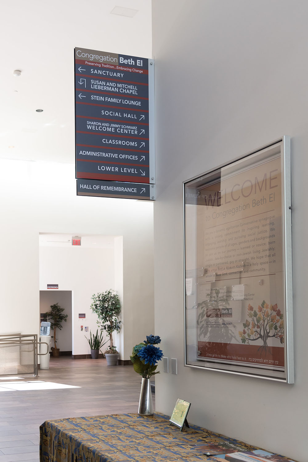 Main lobby way-finding signage. Welcome poster in the foreground; restroom signs in the background