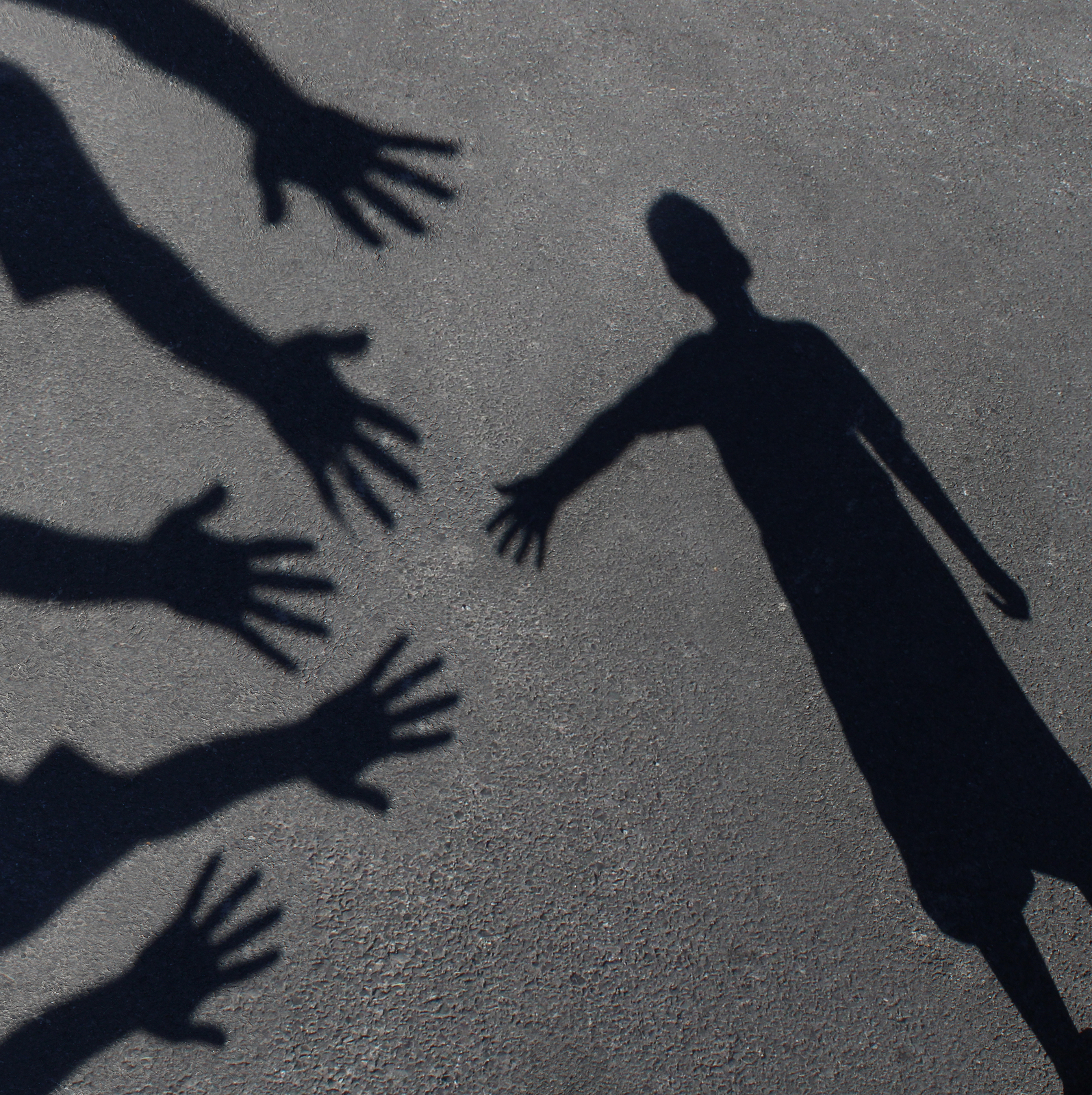 Community support and helping children concept with shadows of a group of extended adult hands offering help or therapy to a child in need as an education symbol of social responsibility t for needy kids and teacher guidance to students who need extra car
