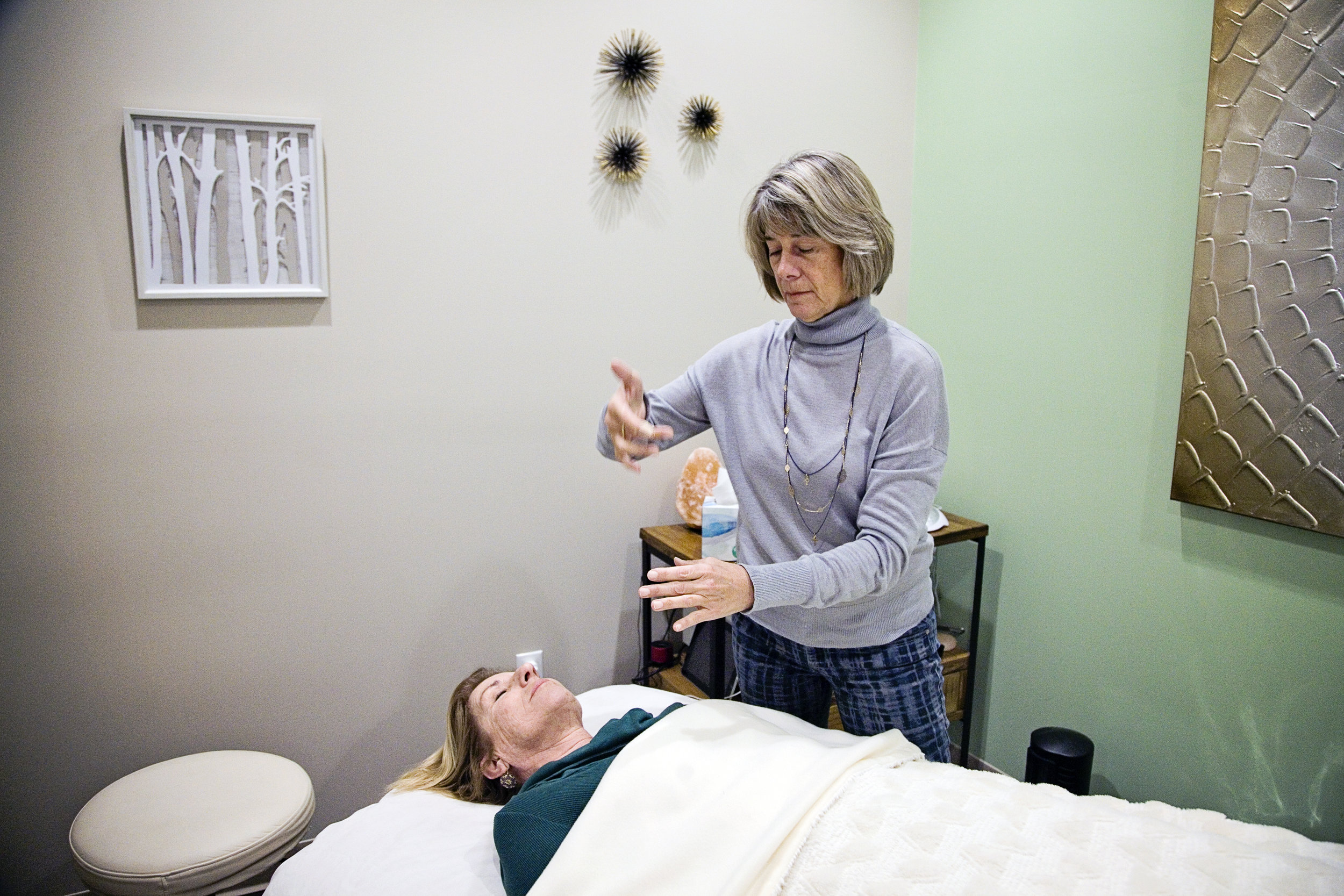 Spiritual Energy Therapist Chris Wheeler, CST conduction an energy therapy session on a client (photo).