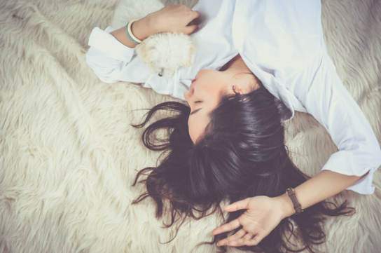 Women laying on fur rug holding puppy .