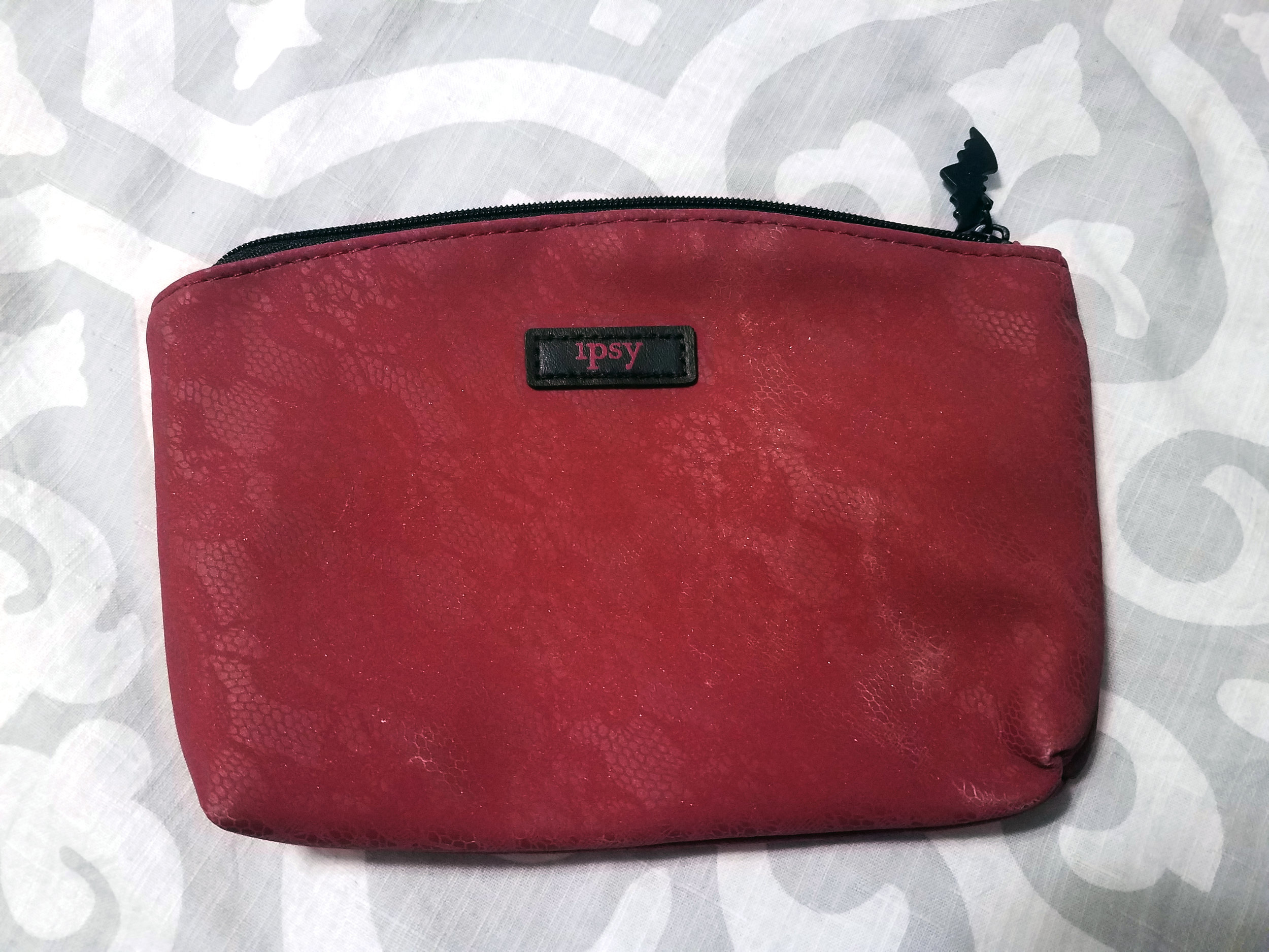 Octobers'bag is red with a lace print on top.It is made of suede and has a little bat pulltab. Reg. Retail Price - $6.25.
