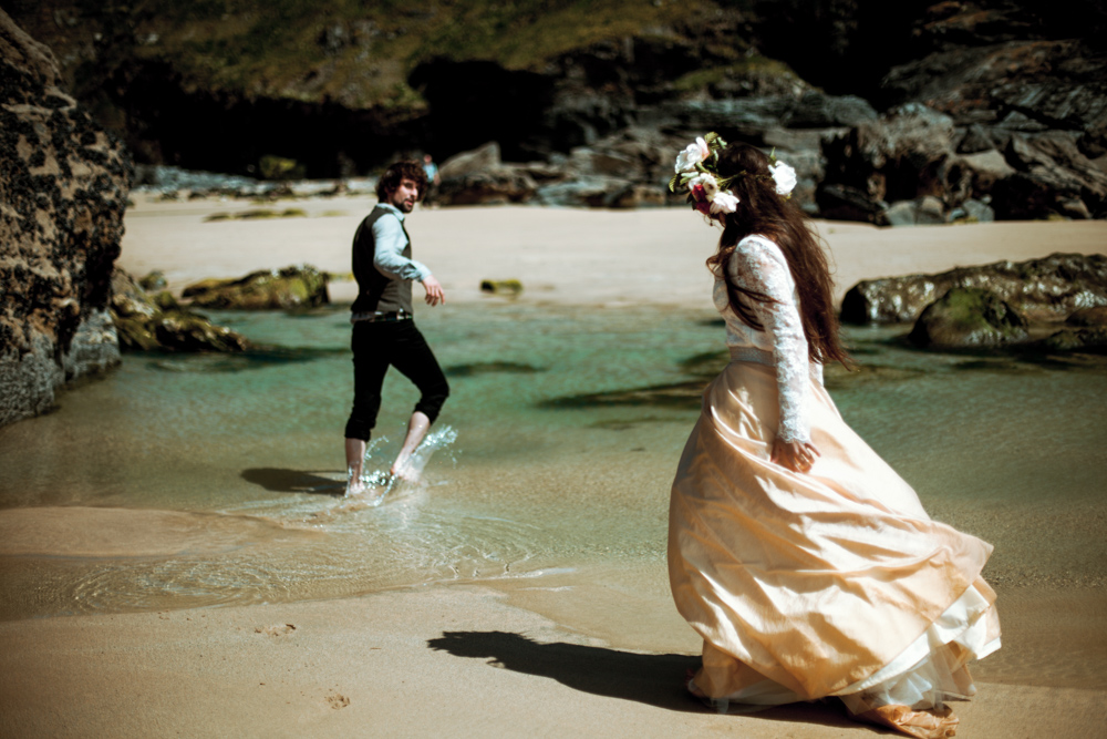 Bride and groom play at the waters edge after their beach elopement.