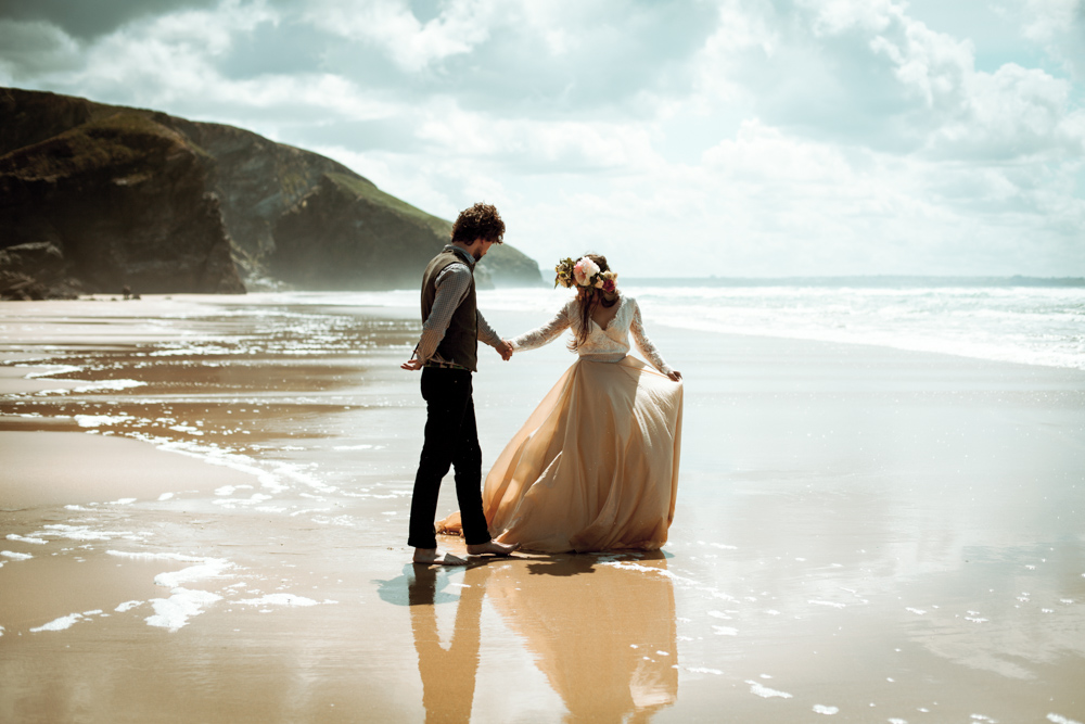 Bride and groom walk in shallow water at the beach in Cornwall.
