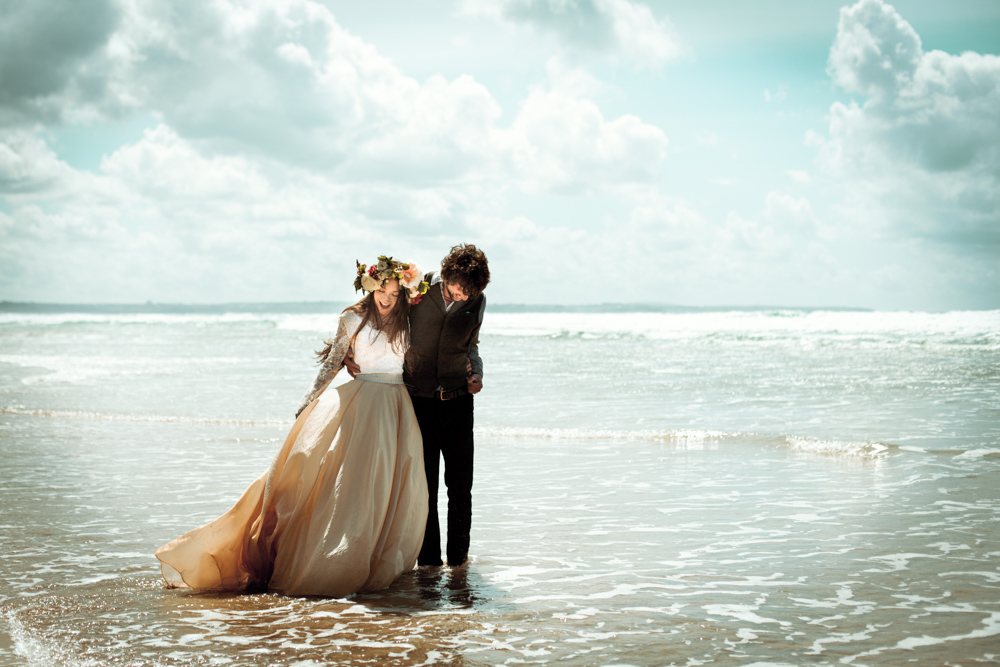 Couple walk together in the waves at their Cornish beach elopement.