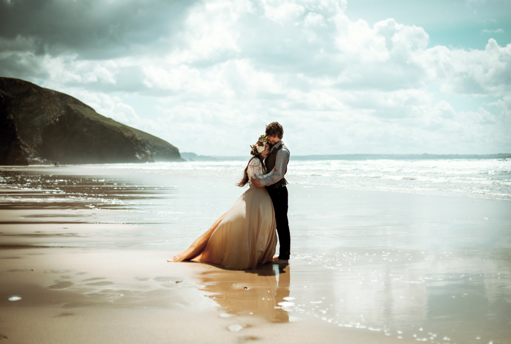 Bride and groom embrace on the beach after their wedding elopement.