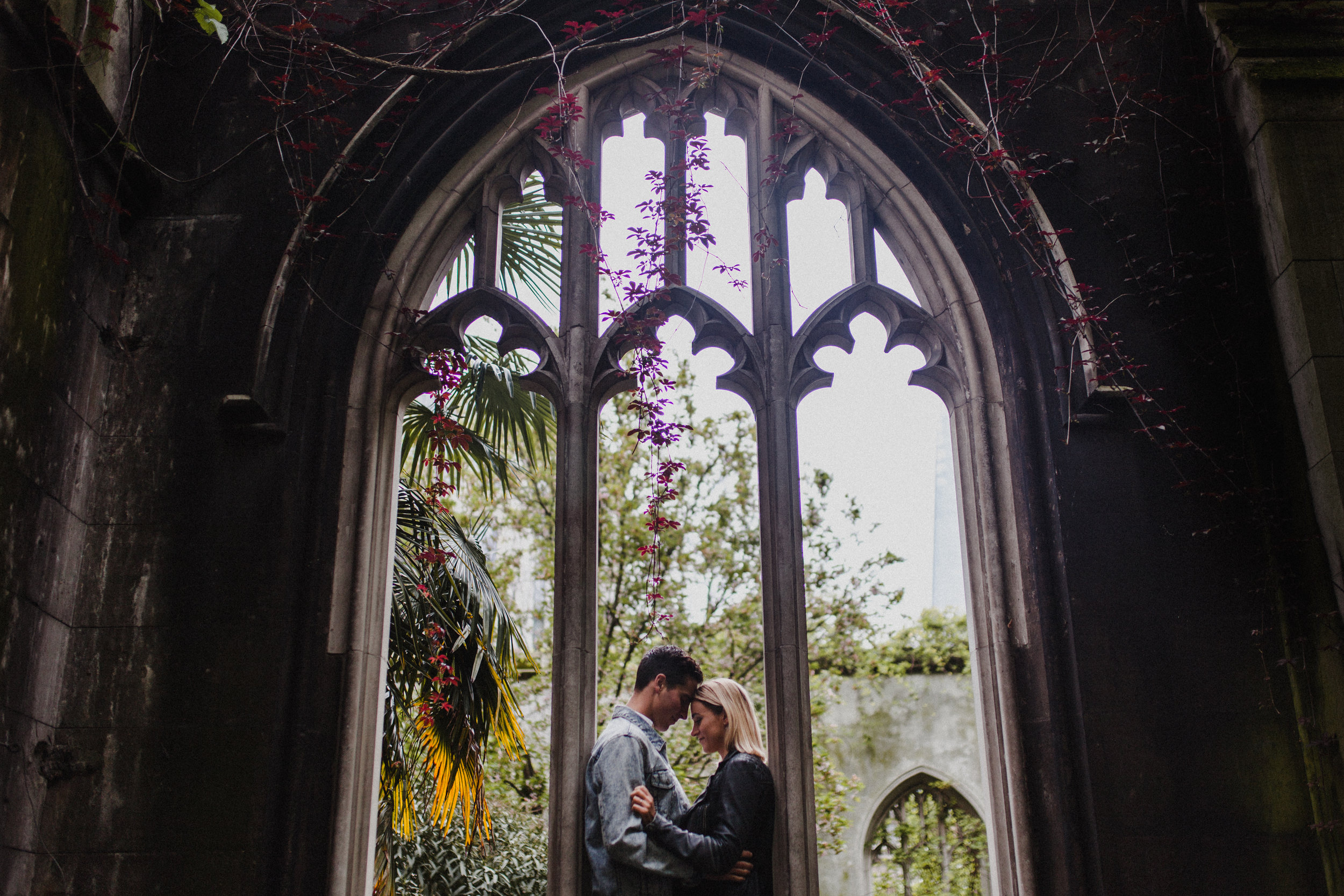 A beautiful stone window frames the couple in this portrait at the gardens at St Dunstan-in-the-East
