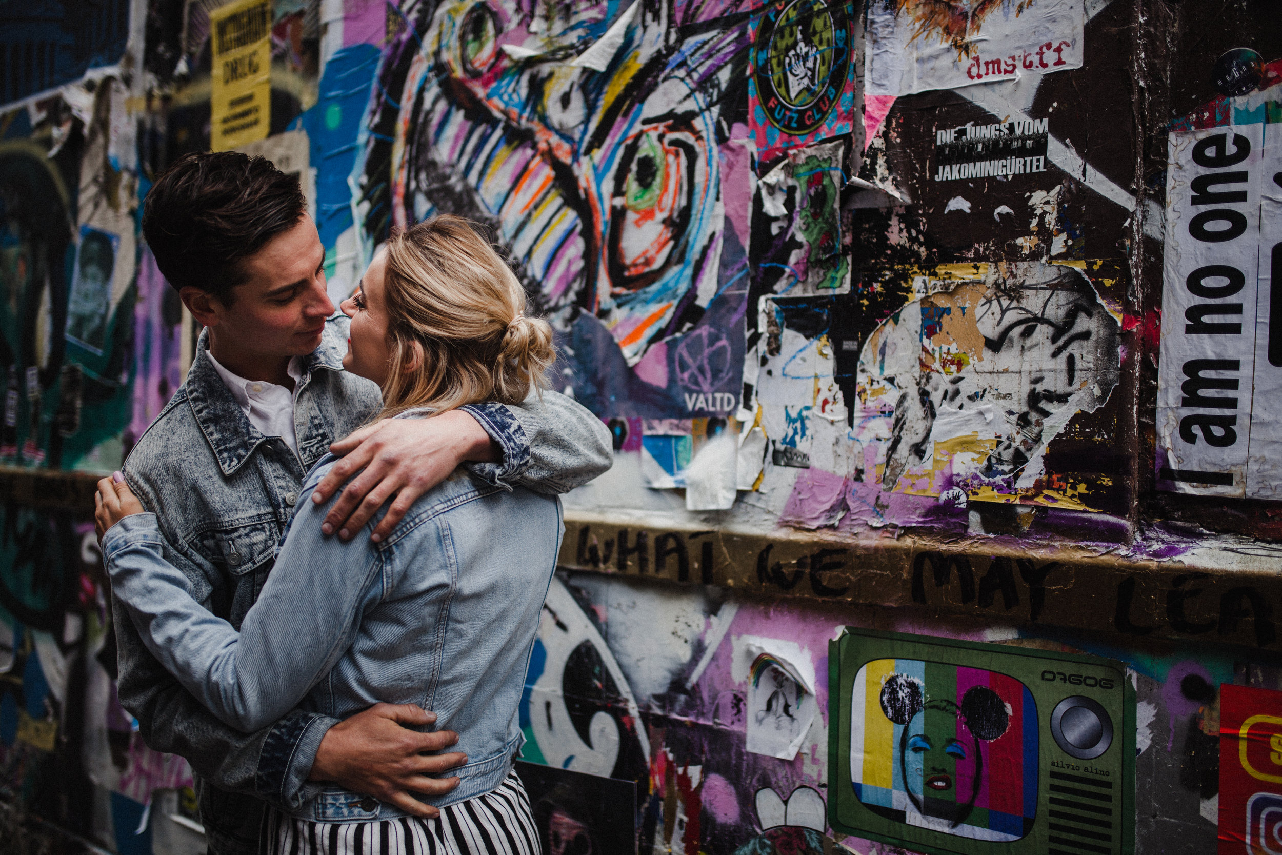 Couple embrace during their couple shoot in Brick Lane, featuring a colourful graffiti wall as a backdrop.