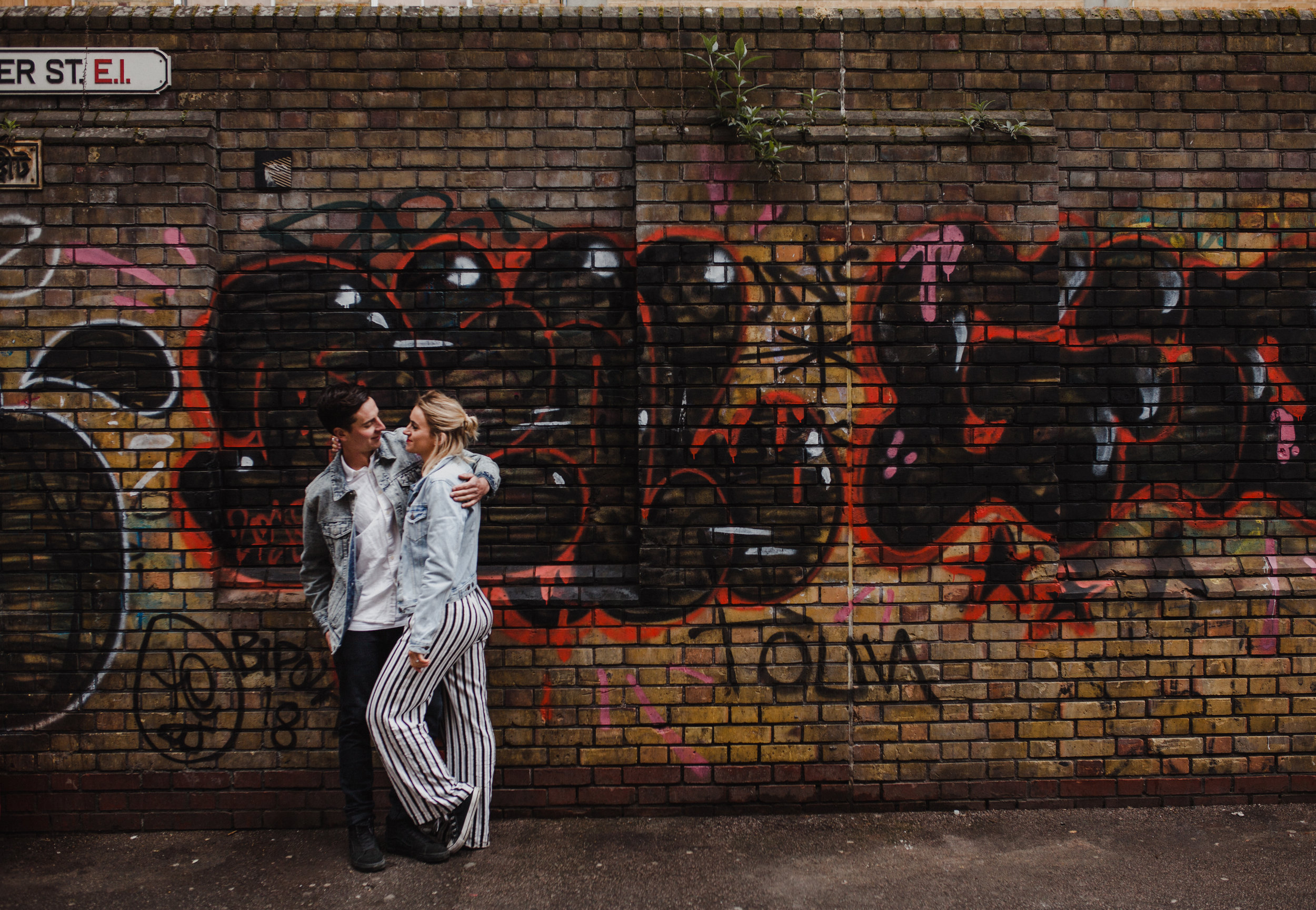 A natural style portrait of couple embracing with a graffiti backdrop.