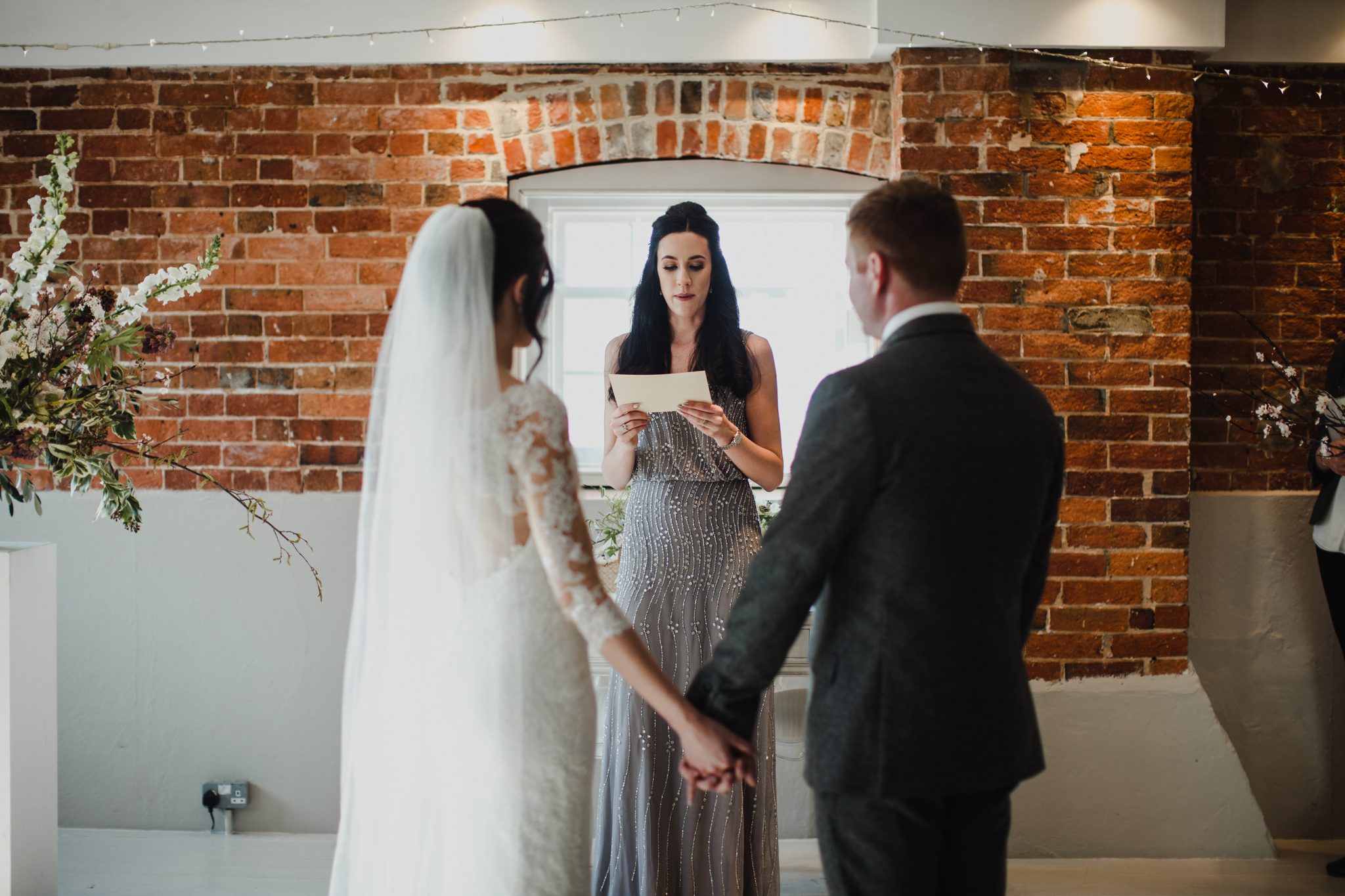 Bride and groom holding hands while a reading is being presented