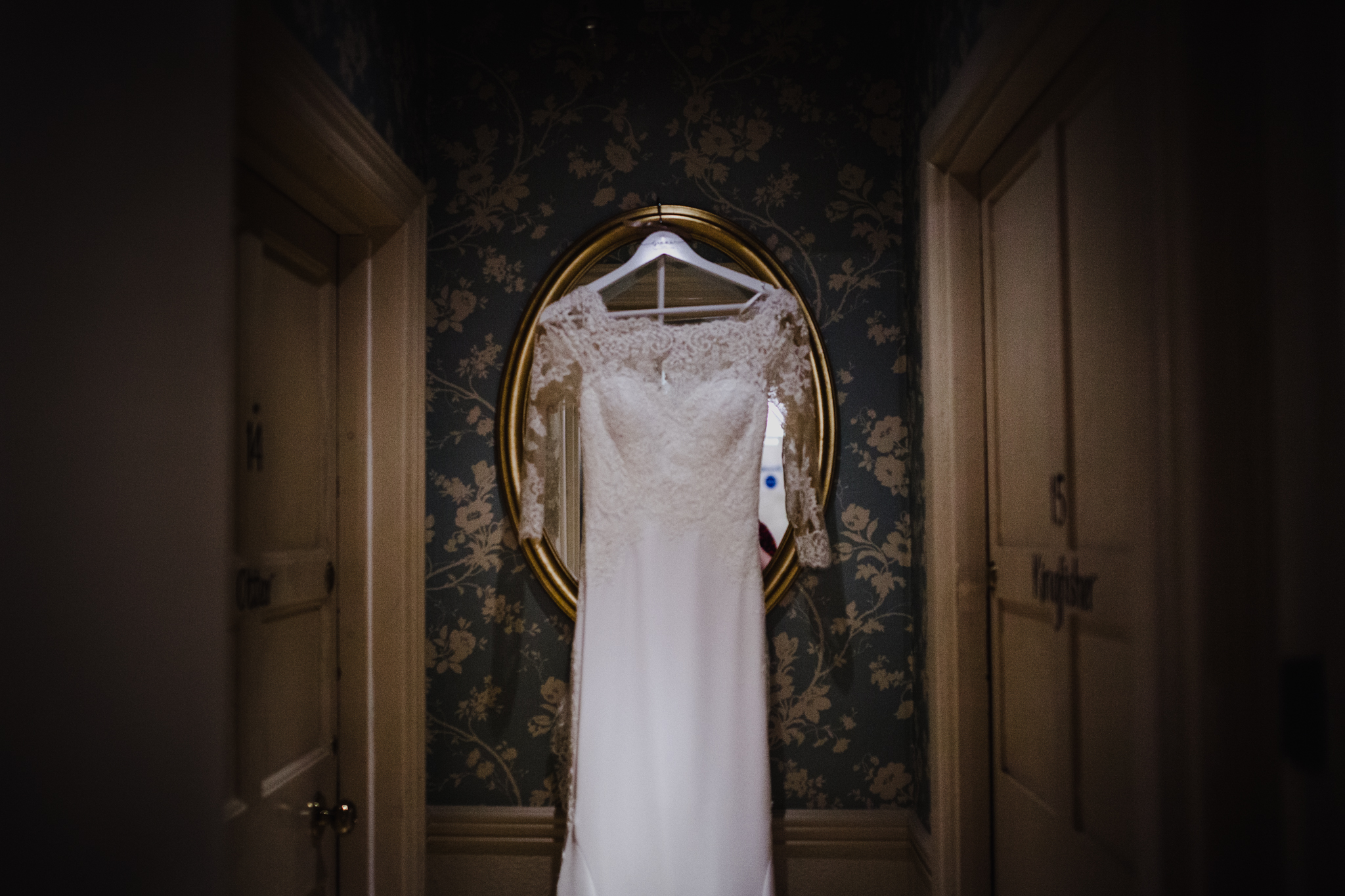 Wedding dress hanging on mirror with patterned wallpaper