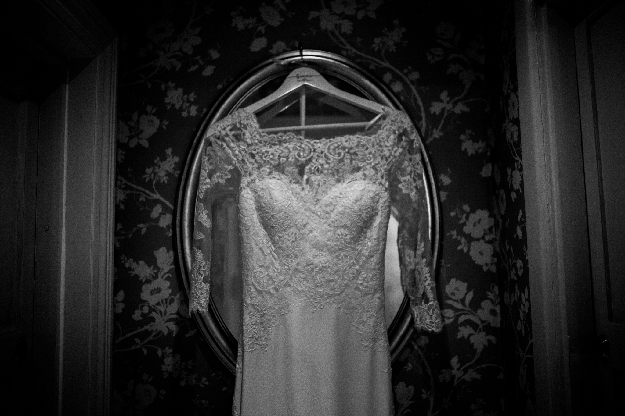 Mirror in hallway with wedding dress hanging on it
