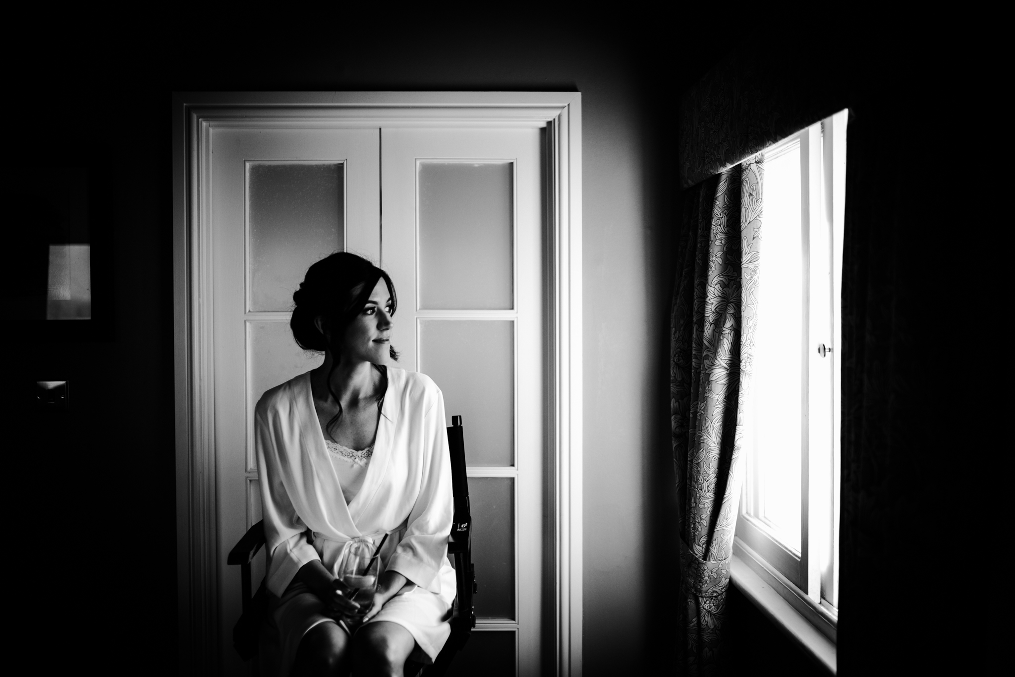 Bride gazing out the window in hotel room